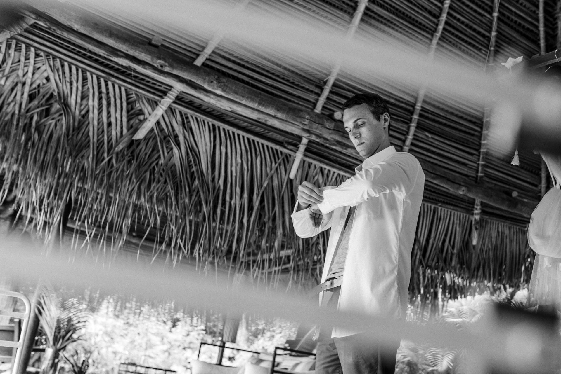 Verana Boutique Homes, Yelapa, Mexique Elopement Picture Story   le marié se prépare pour la cérémonie, en ajustant soigneusement une manche dans son bungalow en bord de mer à Verana Boutique Homes, Yelapa, Mexique