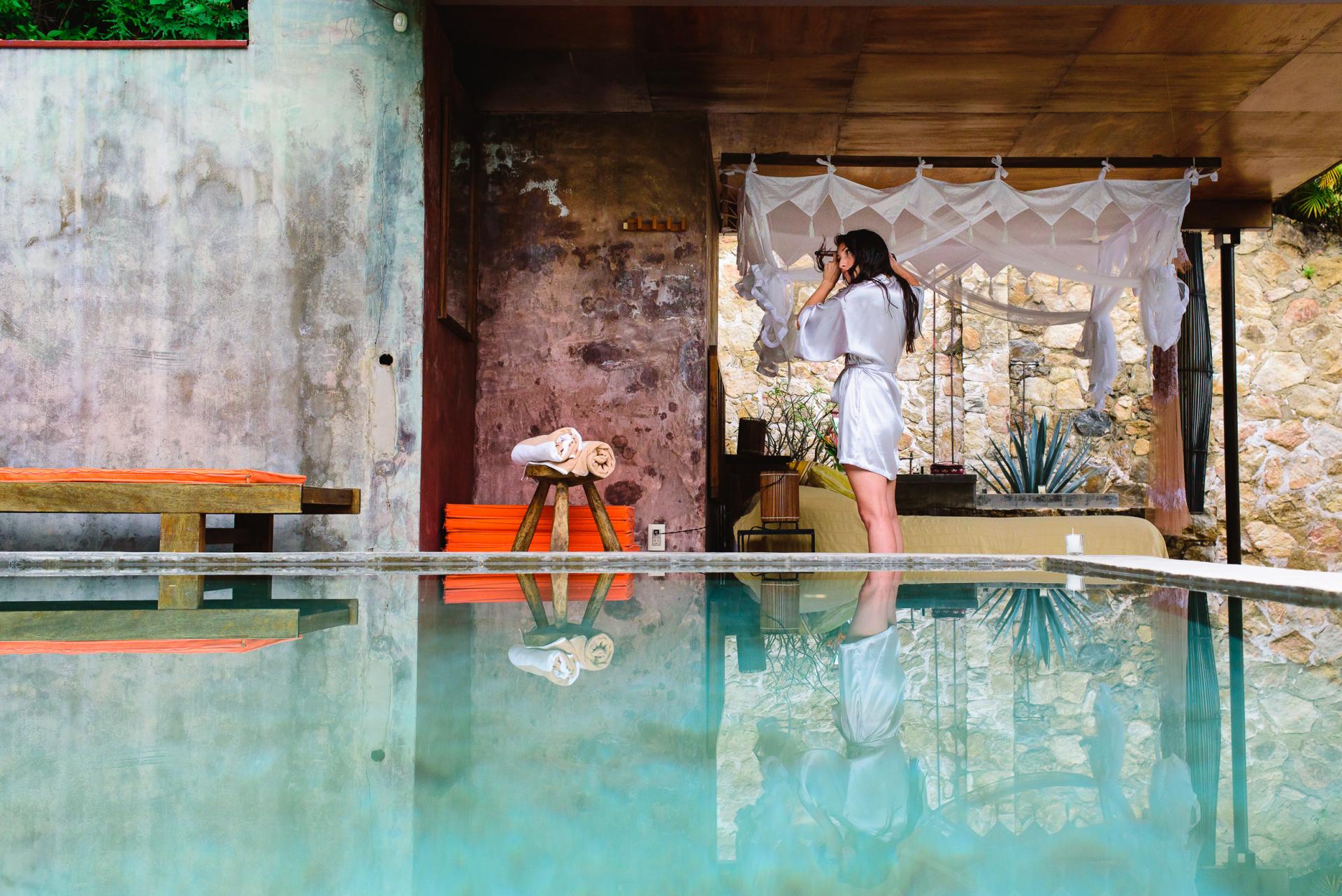 Yelapa, Mexique Elopement de mariage Photos   la mariée se lève, bouclant ses cheveux devant un miroir dans son bungalow aéré et rustique entouré de murs en pierre, d'une piscine claire et remplie de soleil