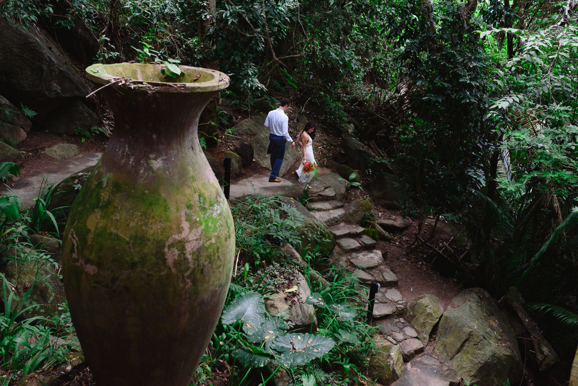 Yelapa, Mexico Elopement Images | the bride and groom head to the ceremony and take their time walking down a beautiful stone staircase surrounded by foliage and hidden behind a massive stone vase
