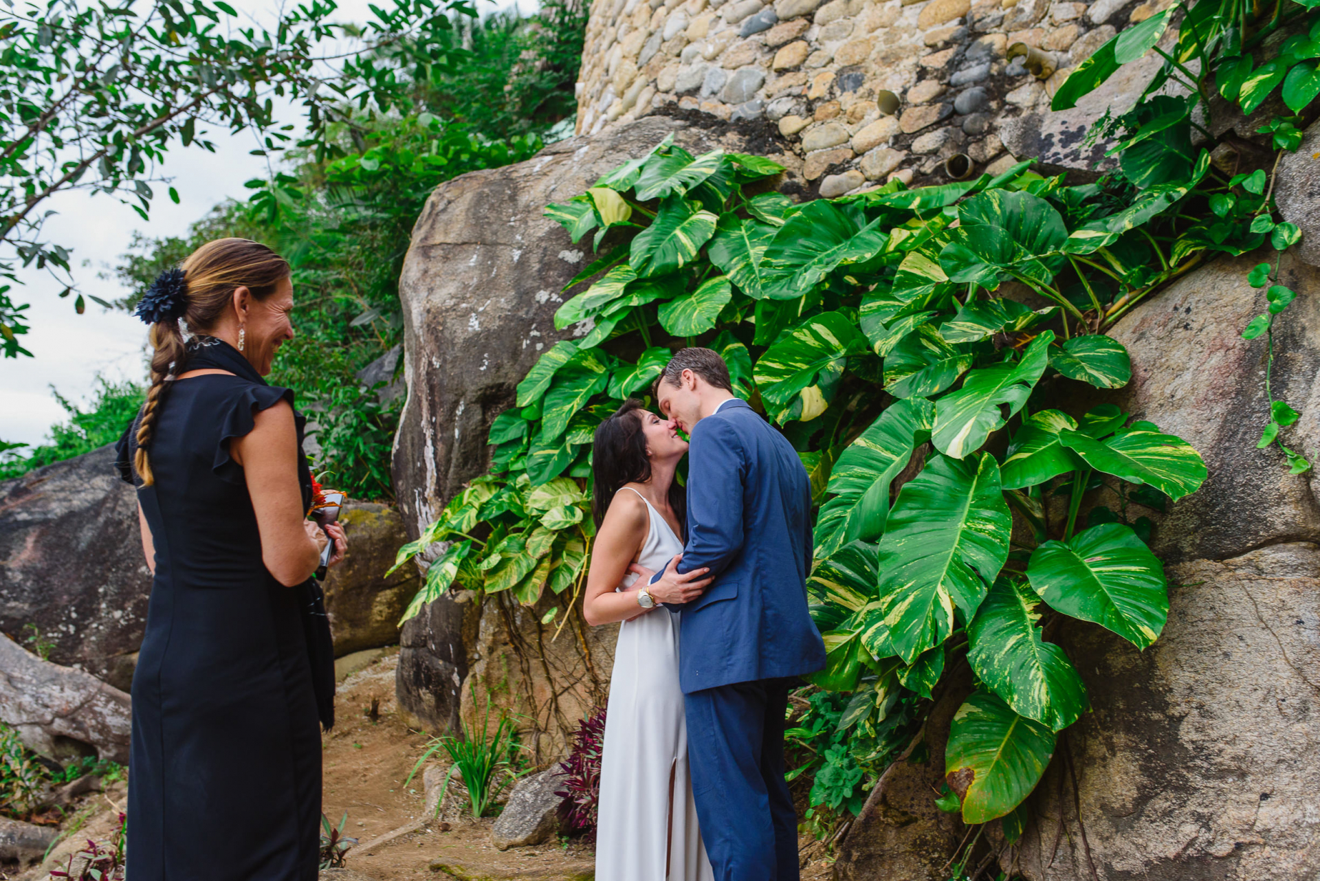 Yelapa, Mexico Elopement Ceremony Picture | The officiant smiles as she gives the couple permission to kiss, concluding this tropical, secluded, and intimate ceremony