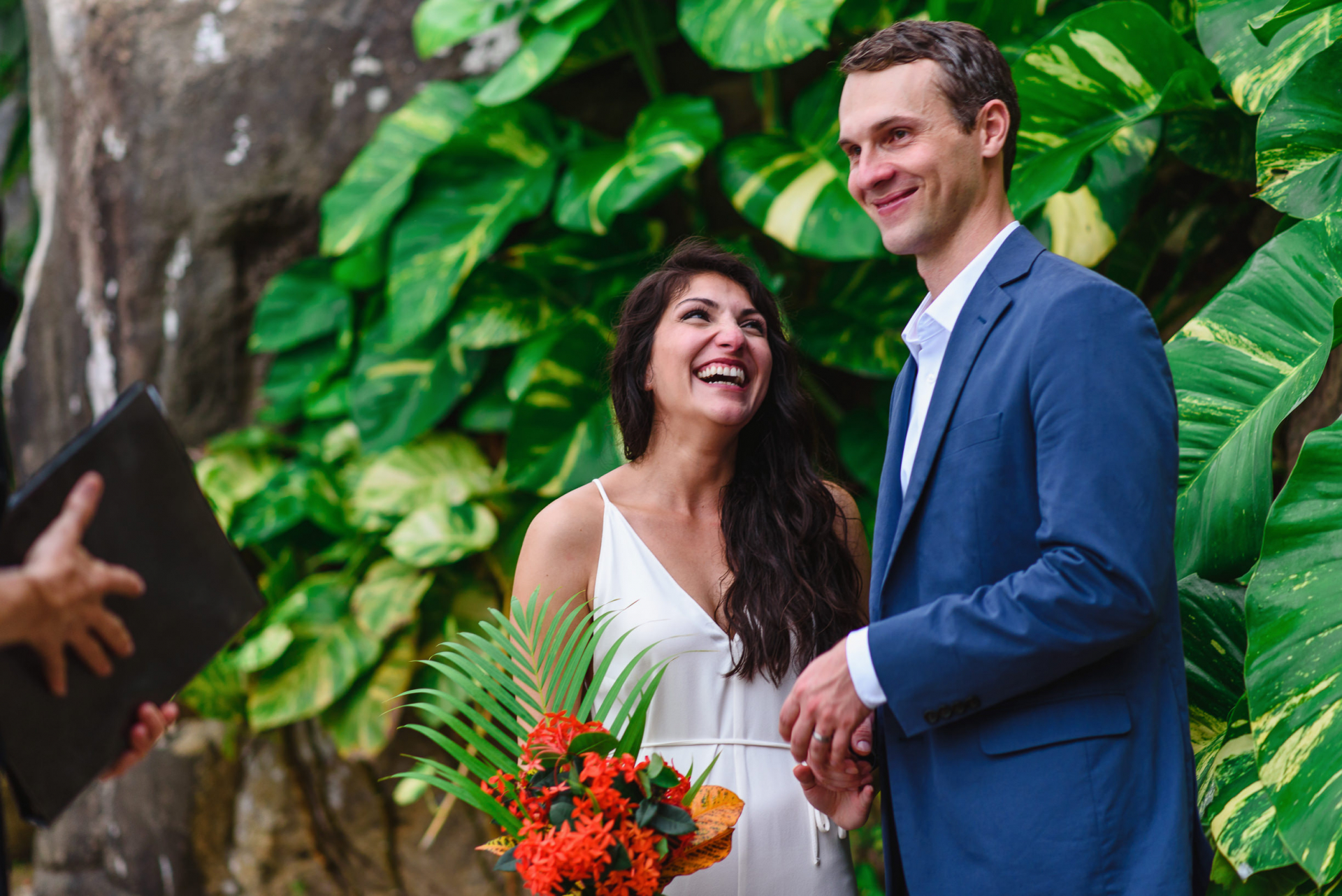 Yelapa, Mexico Bride and Groom Elopement Images | The pair laughs and smiles during the ceremony. They're truly enjoying themselves, surrounded by tropical flora. Even the bride's bouquet sports some lovely orange tropical flowers