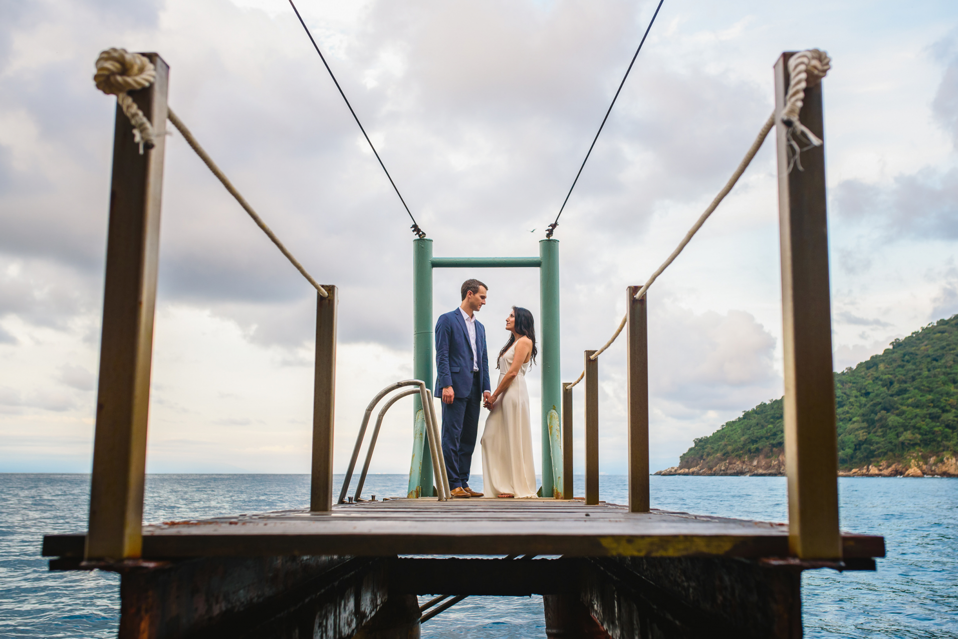 Yelapa, Mexico Elopement Wedding Portrait | The newlyweds gaze longingly into one another's eyes and hold hands as they stand on a dock floating on gleaming blue water