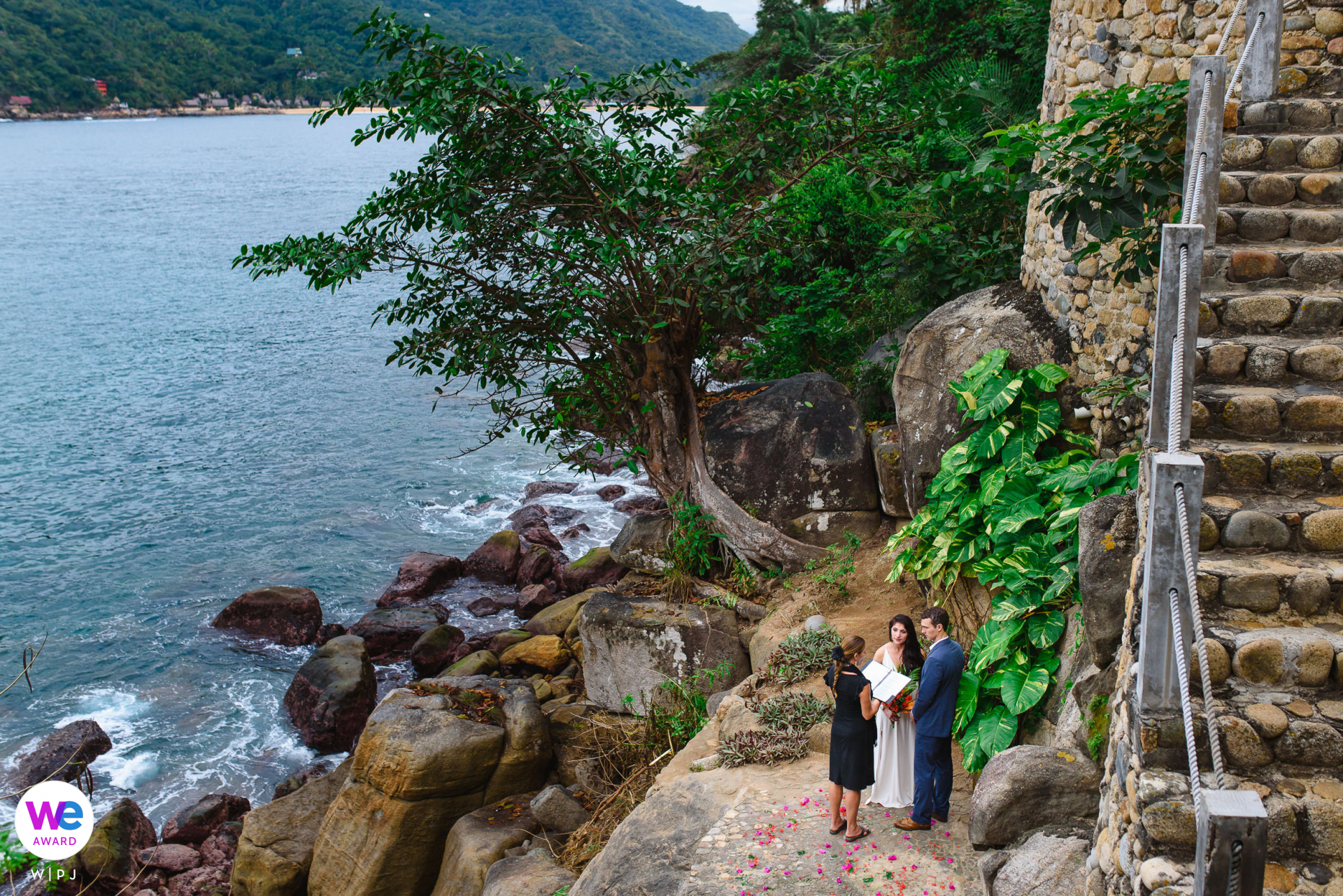 Yelapa, Mexico Beach Elopement Photography Story | married outside surrounded by flower petals beside a rocky beach and blue water at Verana in Yelapa, Mexico