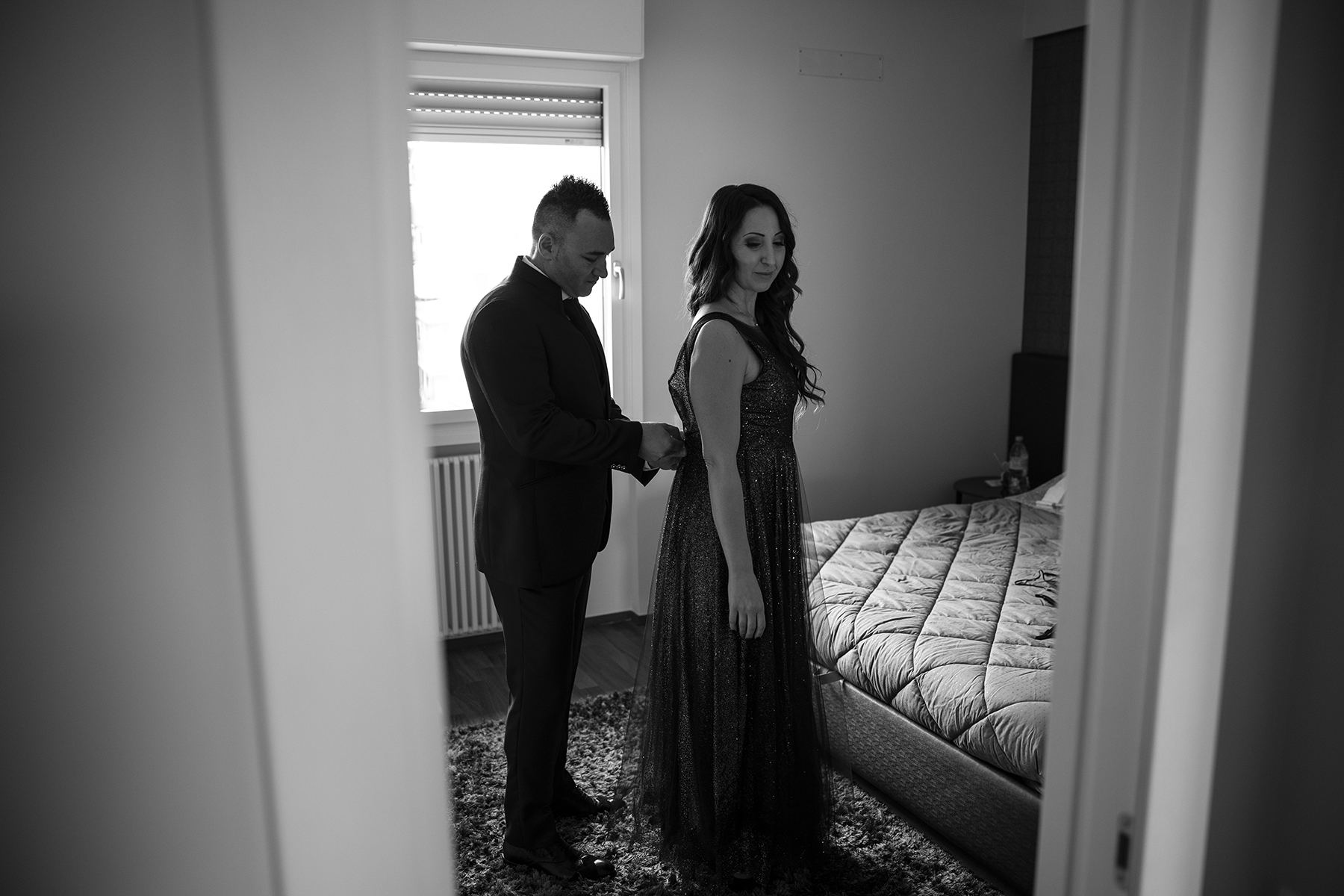 Histoire de photographie de La Spezia Elopement   Regardant autour de la porte de la chambre, nous pouvons voir le marié aider la mariée à refermer sa robe dans le dos