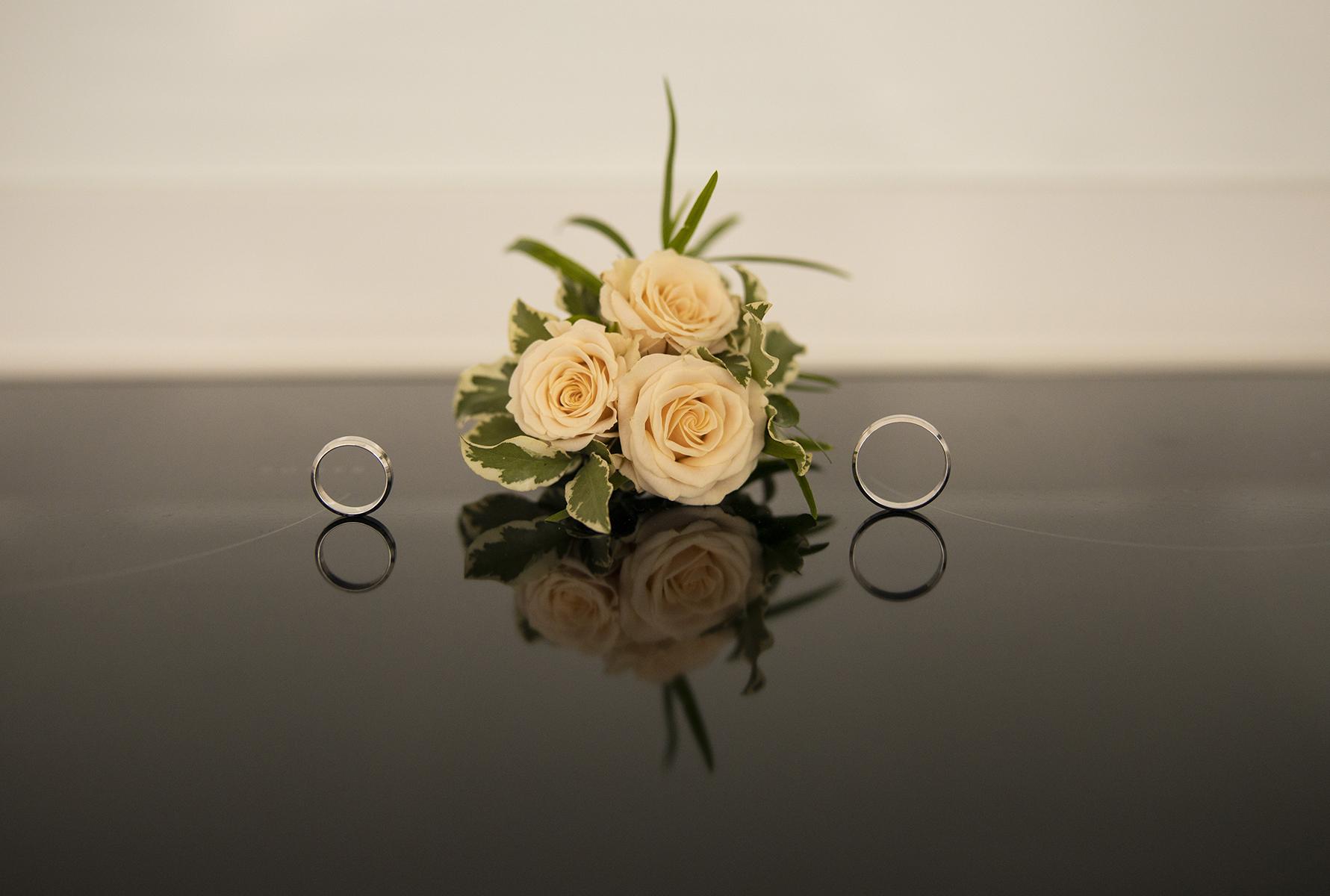 La Spezia Elopement Detail Photo   Le bouquet de roses de la mariée est assis sur une table en forme de miroir à côté des deux alliances