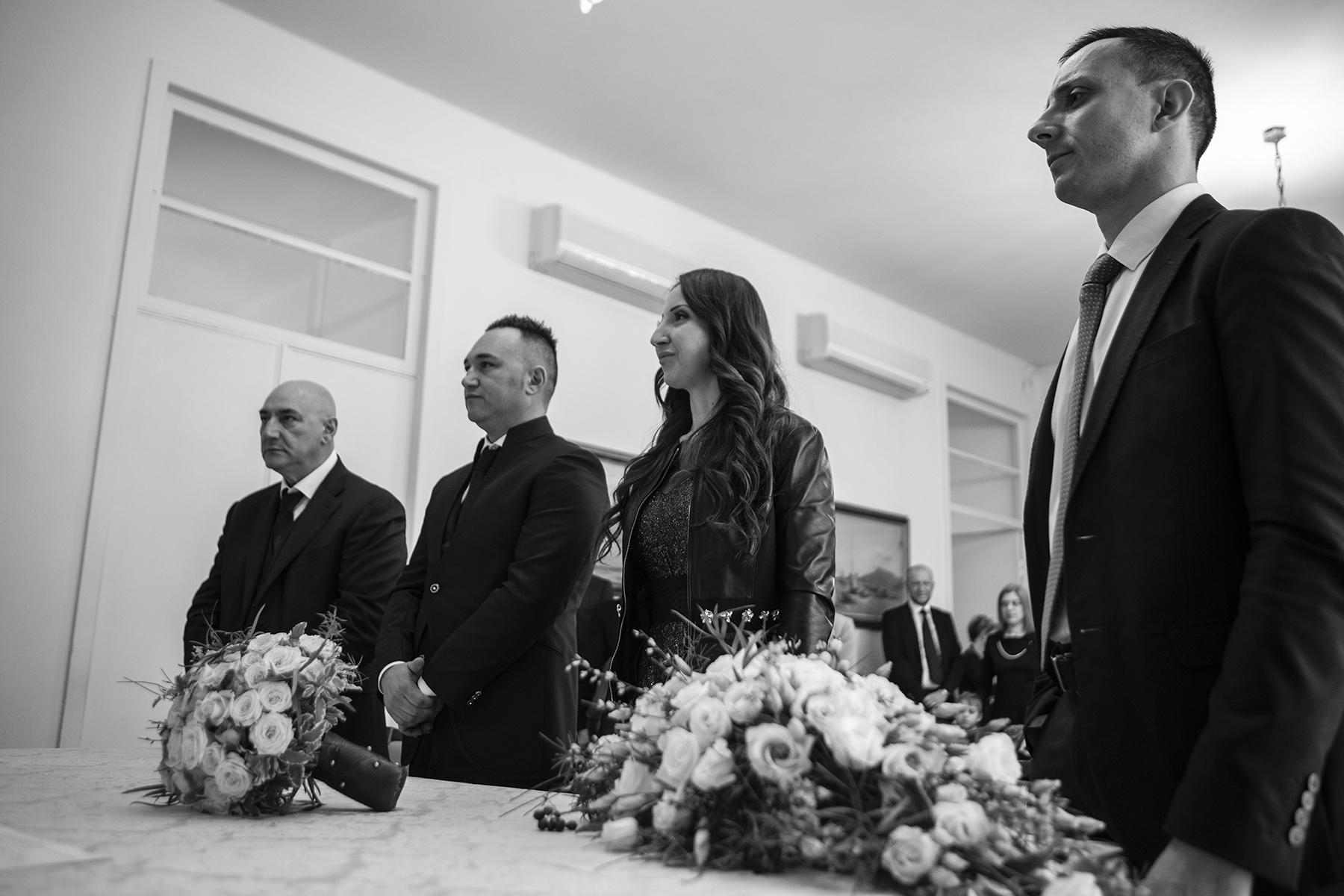 Cérémonie d'élimination de La Spezia Image   La mariée et le marié se tiennent ensemble à l'autel, qui est décoré de beaux bouquets de fleurs. Pendant qu'ils se lèvent, écoutant l'officiant, leurs invités regardent derrière eux