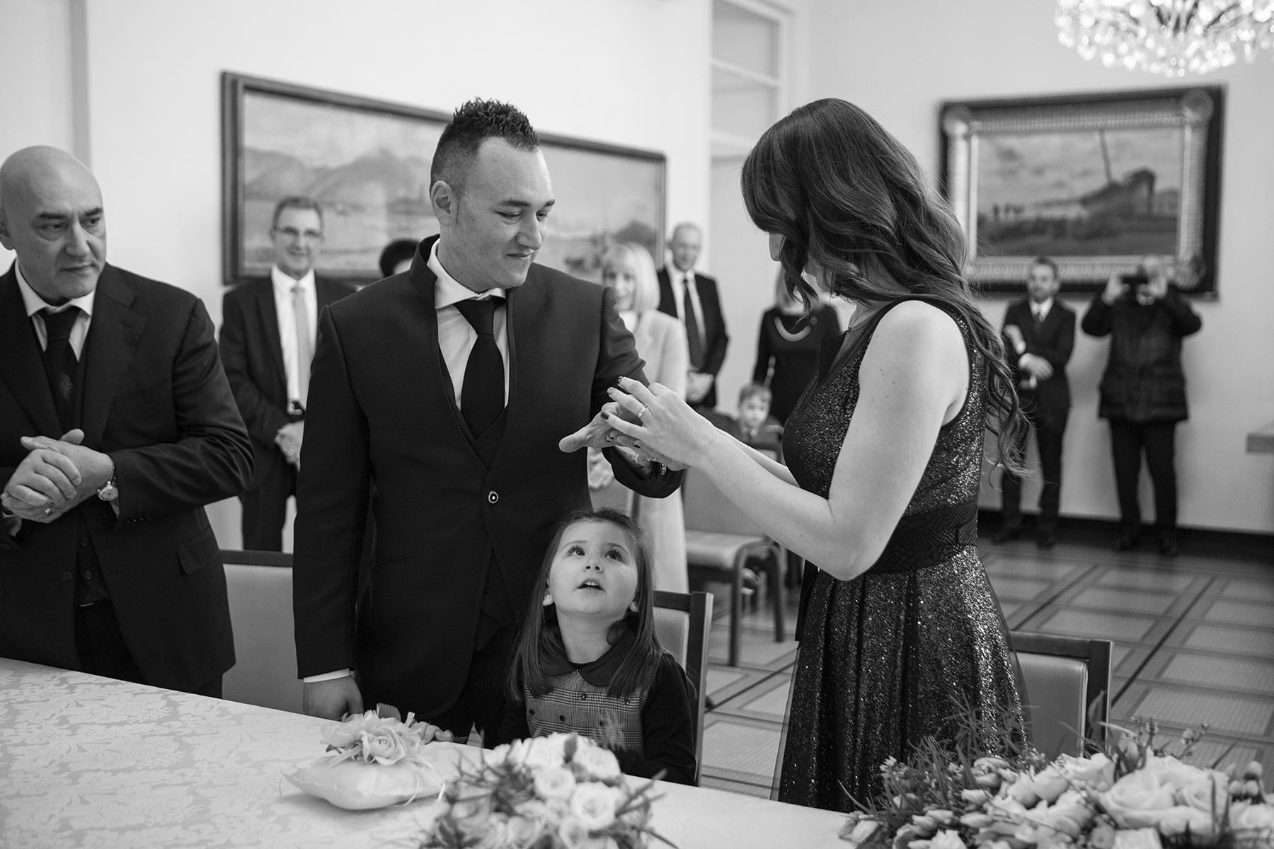 Photo de la cérémonie de mariage de La Spezia Elopement   Une petite fille regarde curieusement sous la main du marié, le regardant alors que la mariée met sa bague