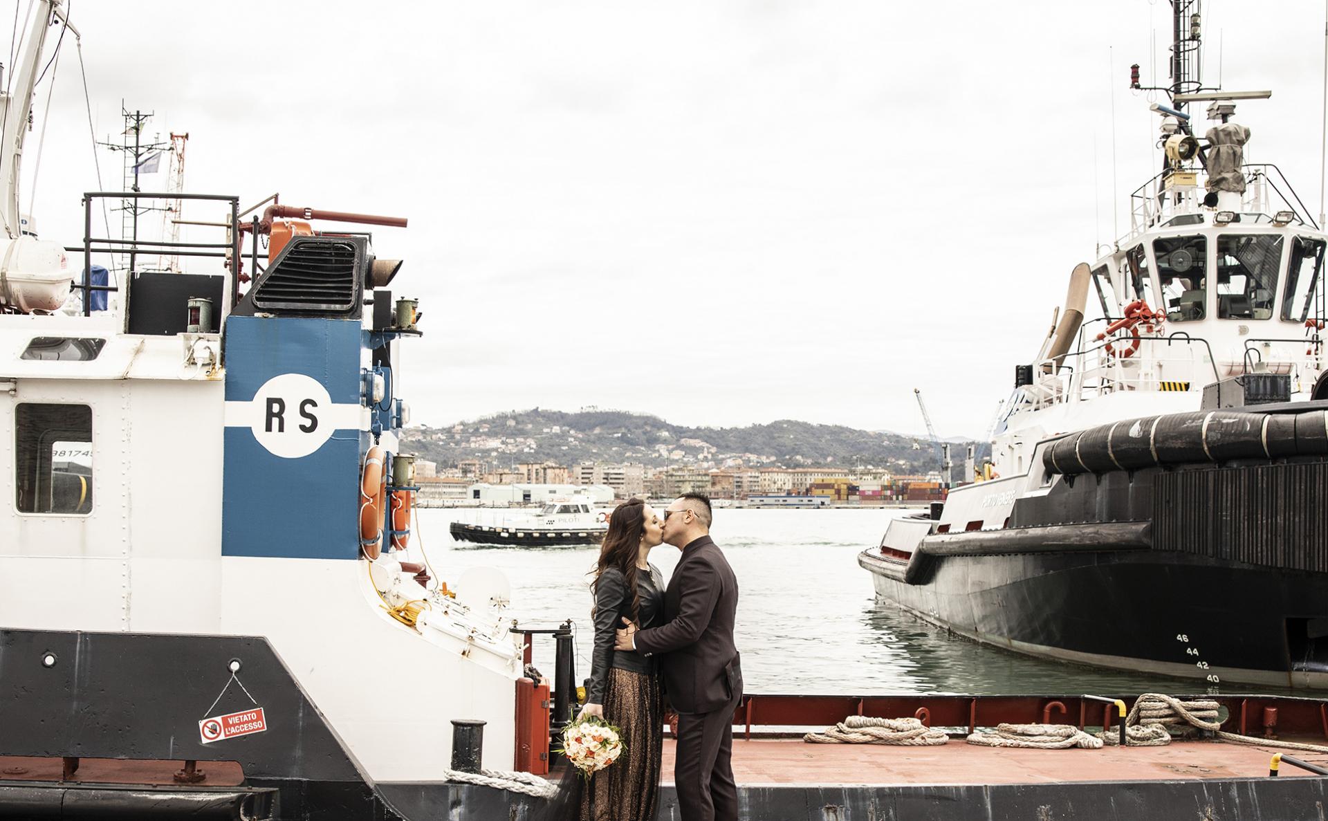 La Spezia Elopement Portrait du couple   Les jeunes mariés se tiennent ensemble sur un bateau, flottant sur une rivière