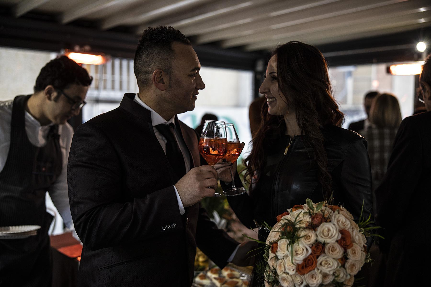 Image de La Spezia Elopement - Moment pour le couple   À la réception au Bar Peola, les mariés ont un moment privé en se faisant griller avec leurs verres de vin