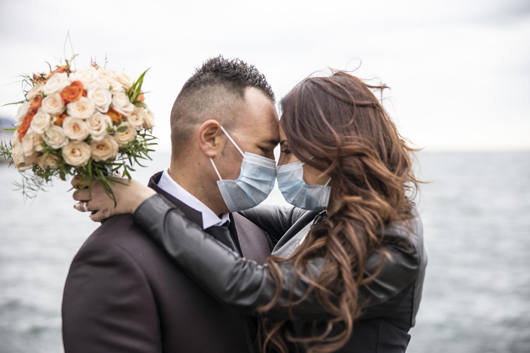 Portrait de couple La Spezia Elopement   La mariée et le marié s'embrassent et touchent leurs fronts ensemble, séparés uniquement par leurs masques faciaux