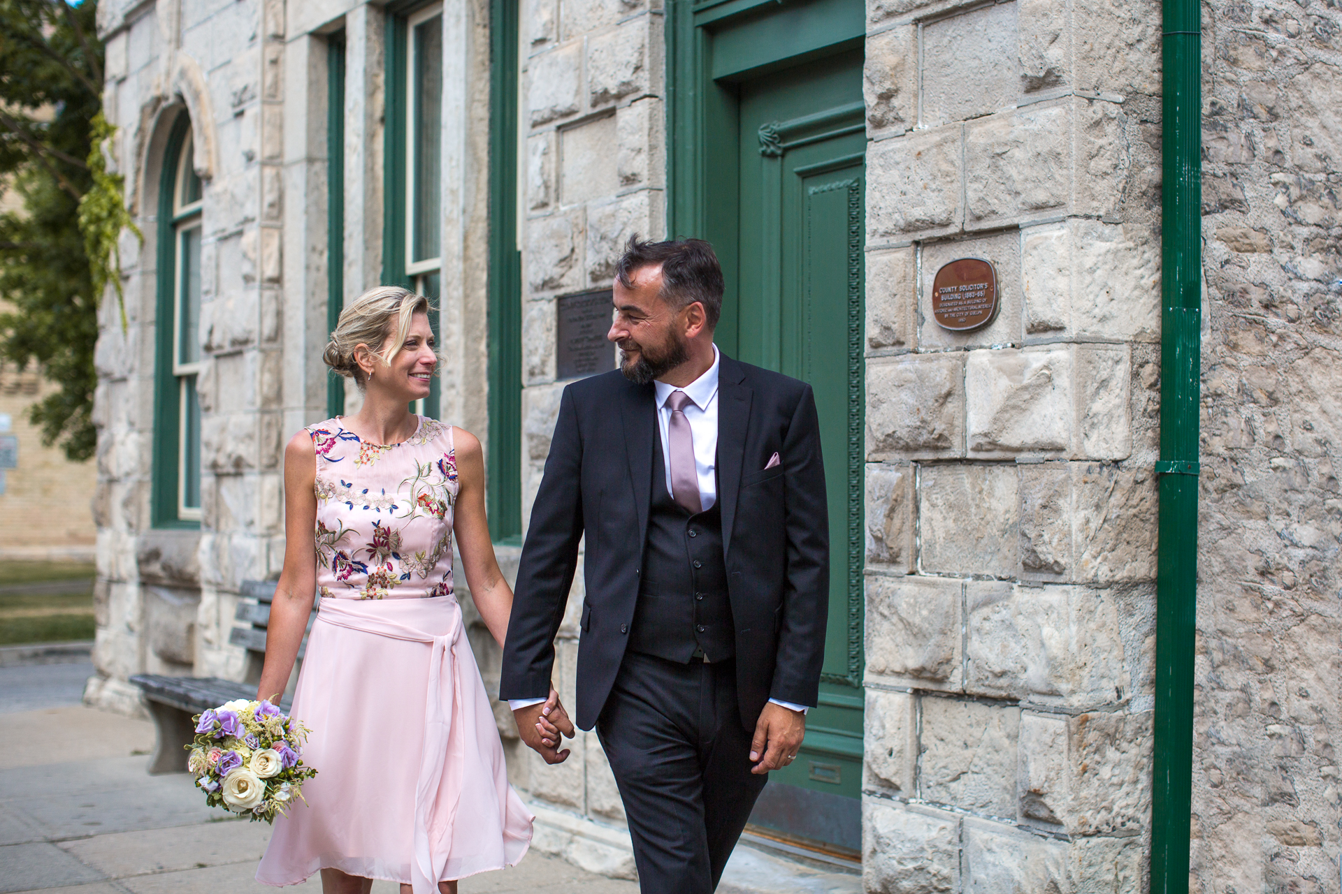 Ontario, Canada Elopement Bride and Groom Walking Portrait | The happy couple walk down the streets of Guelph just after the ceremony