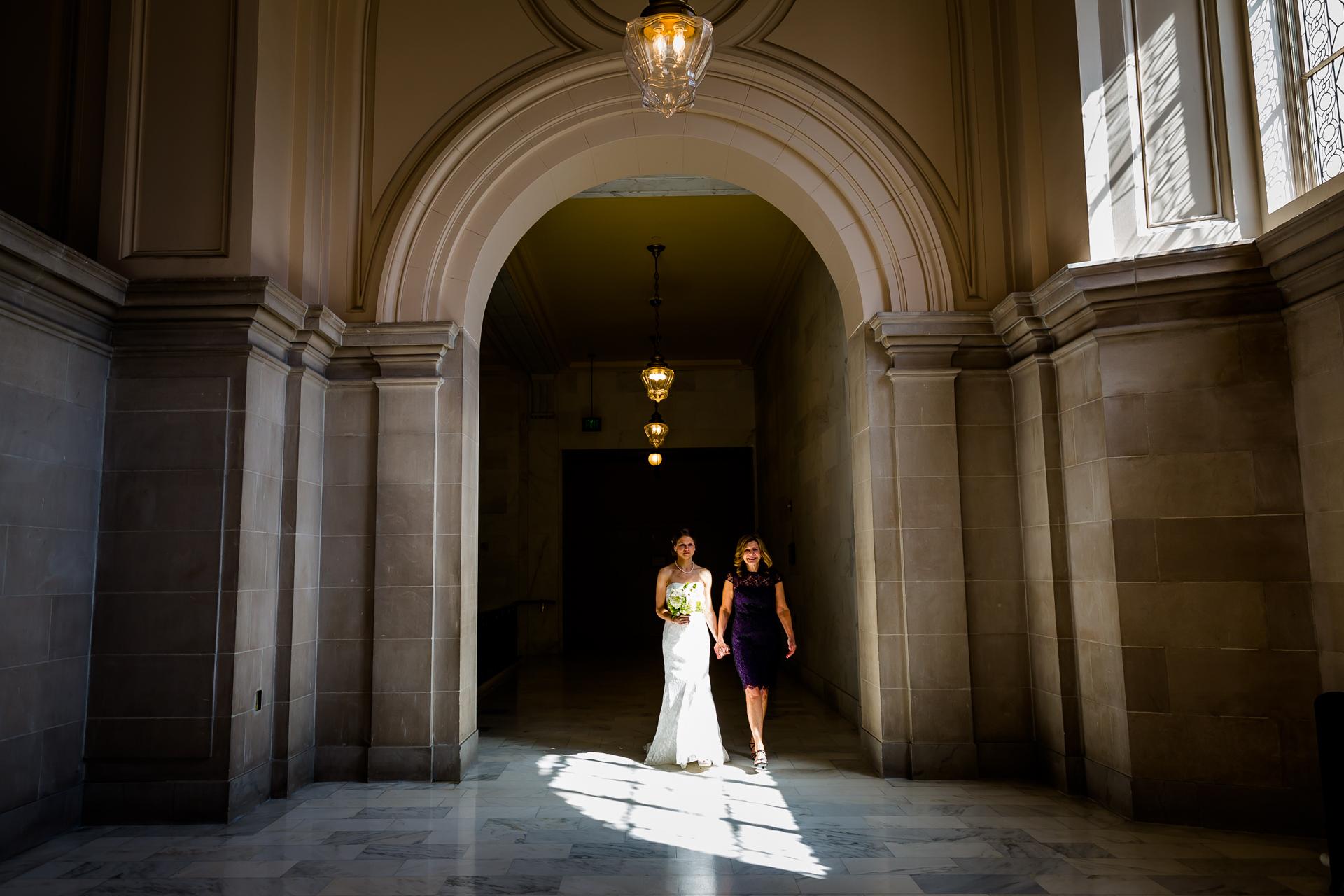 Foto de Elopement de boda pequeña en San Francisco   La luz de la tarde brilló en el pasillo iluminando a la novia que ya brillaba mientras caminaba hacia la ceremonia.
