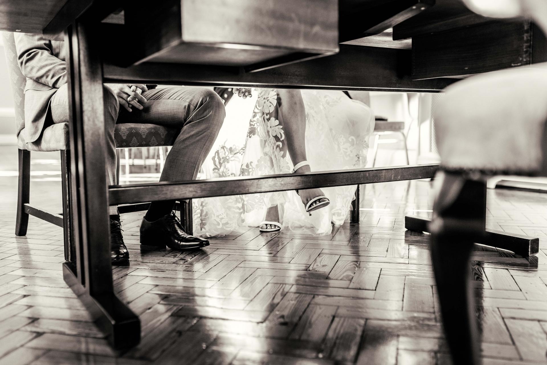 Richmond upon Thames, London Elopement Fotografie | Ungewöhnliches Hochzeitsfoto des Bräutigams und der Brautbeine, als die Braut ein wunderschönes Spitzenhochzeitskleid mit passenden offenen Zehenschuhen trug