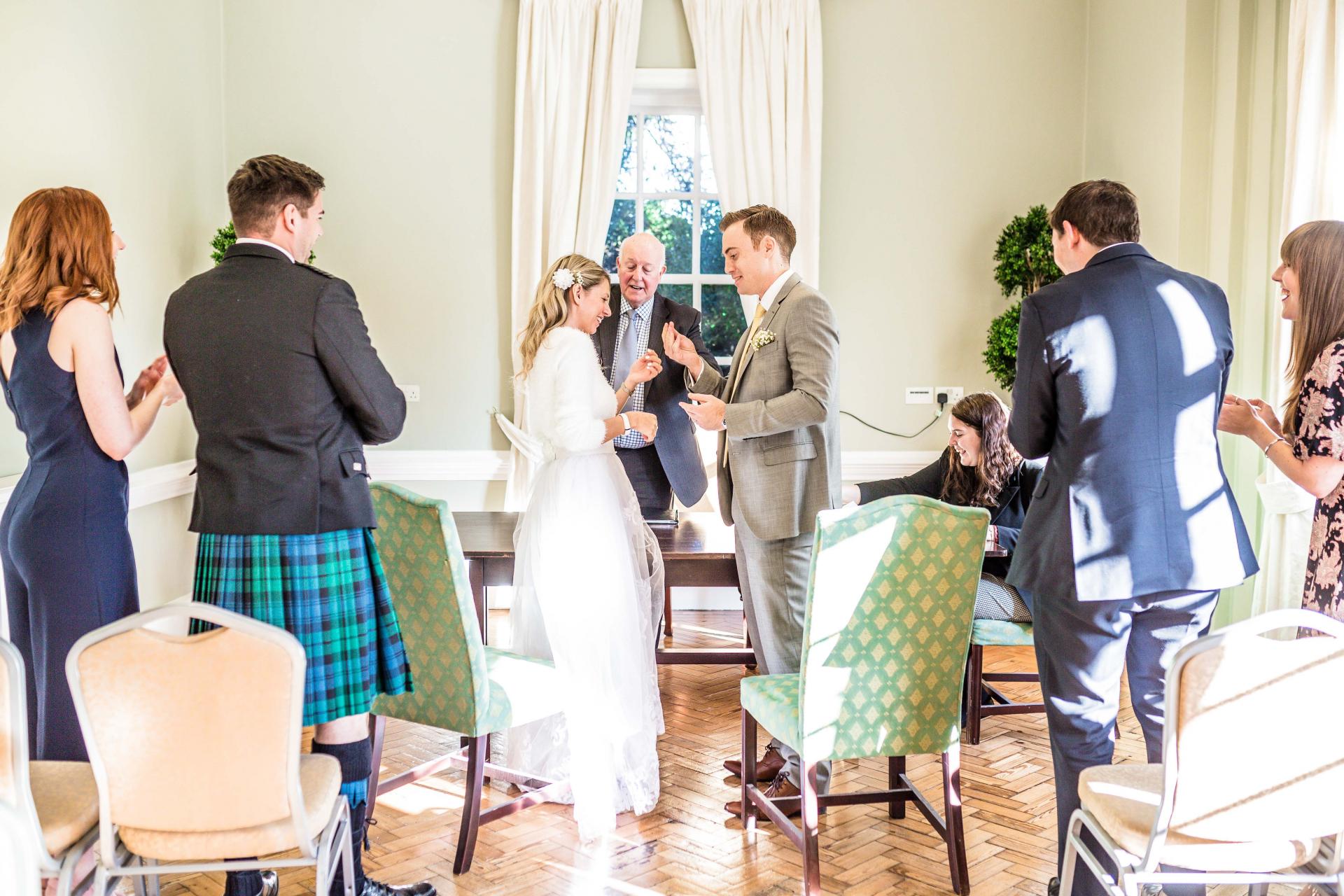 York House Twickenham, London Elopement Zeremonie Bild | Braut und Bräutigam werden als Ehefrau und Ehemann ausgesprochen, während die erste Reihe der Gäste sie anfeuert