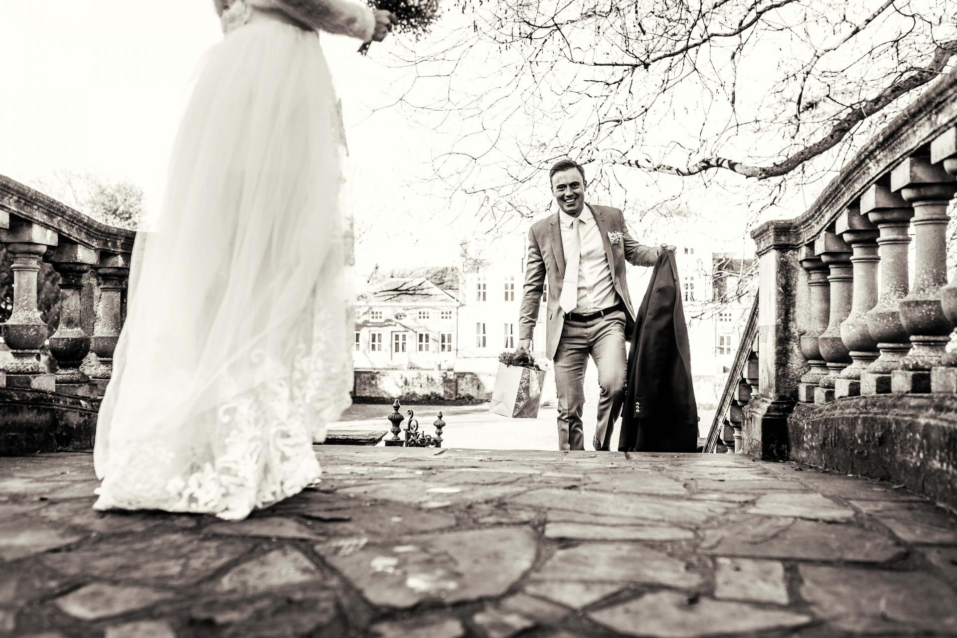 London Elopement Paar Fotografie | Der englische Herr trägt Blumen und Jacke für seine Frau, falls seine Frau kalt wird