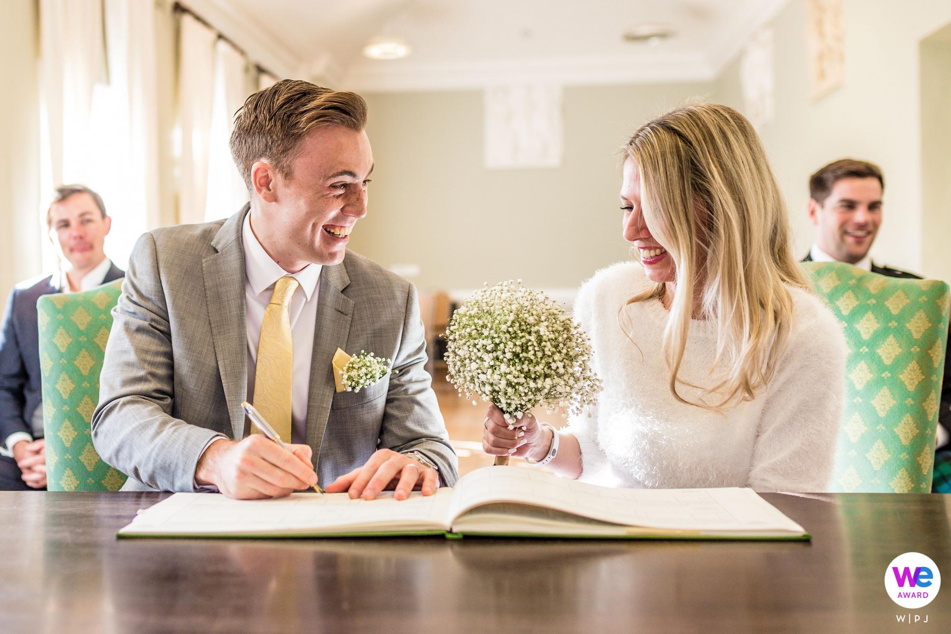 York House Twickenham, Richmond nach Themse, London Elopement Picture Story | Nachdem das Hochzeitspaar offiziell als Ehemann und Ehefrau bezeichnet wird, muss ein Heiratsregister mit den Angaben des Paares unterschrieben werden