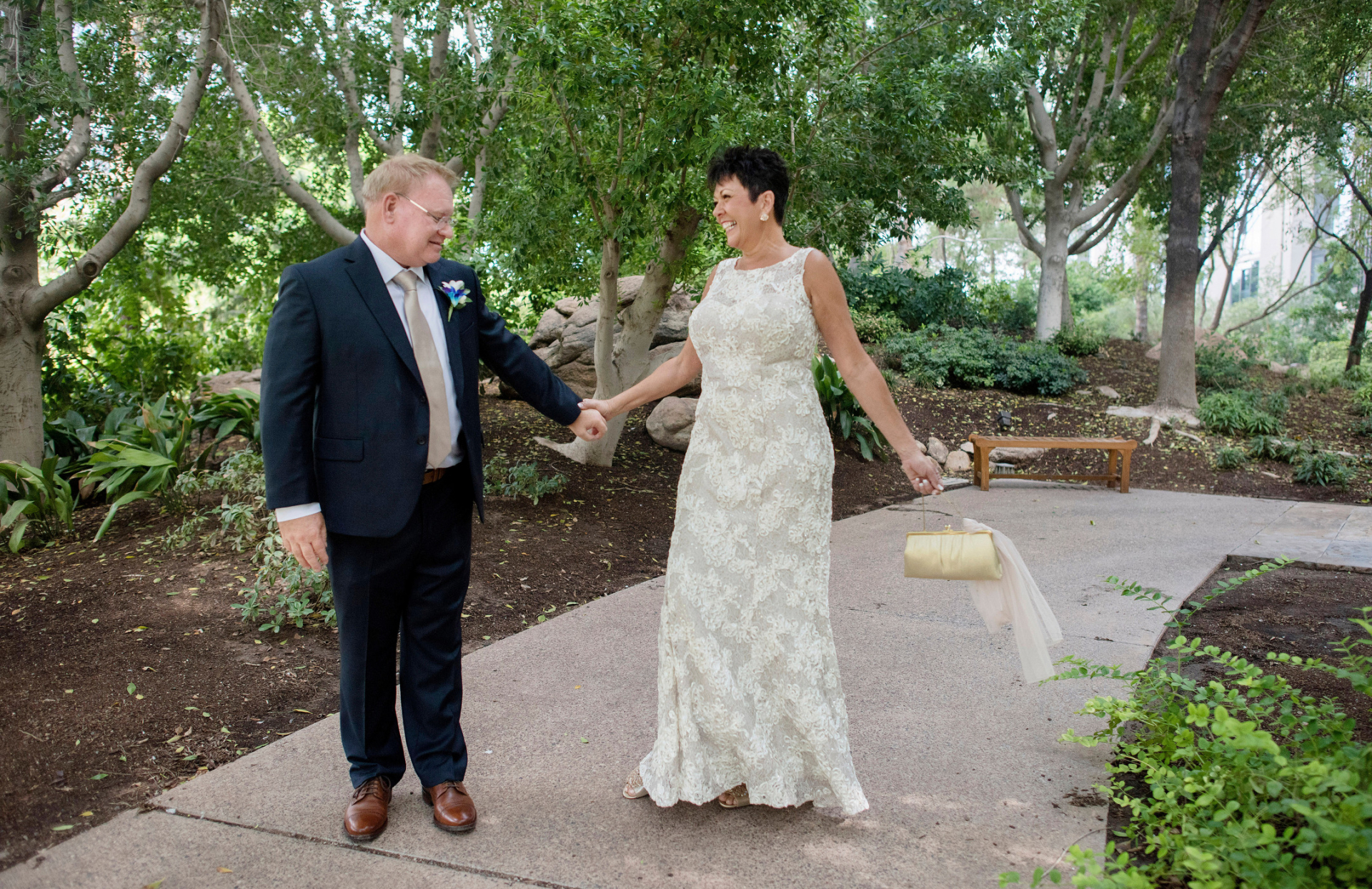 Japanese Friendship Garden, Phoenix, AZ Elopement Photography | The bride grabs the groom's hand, a huge smile on her face, as she happily swings her clutch.