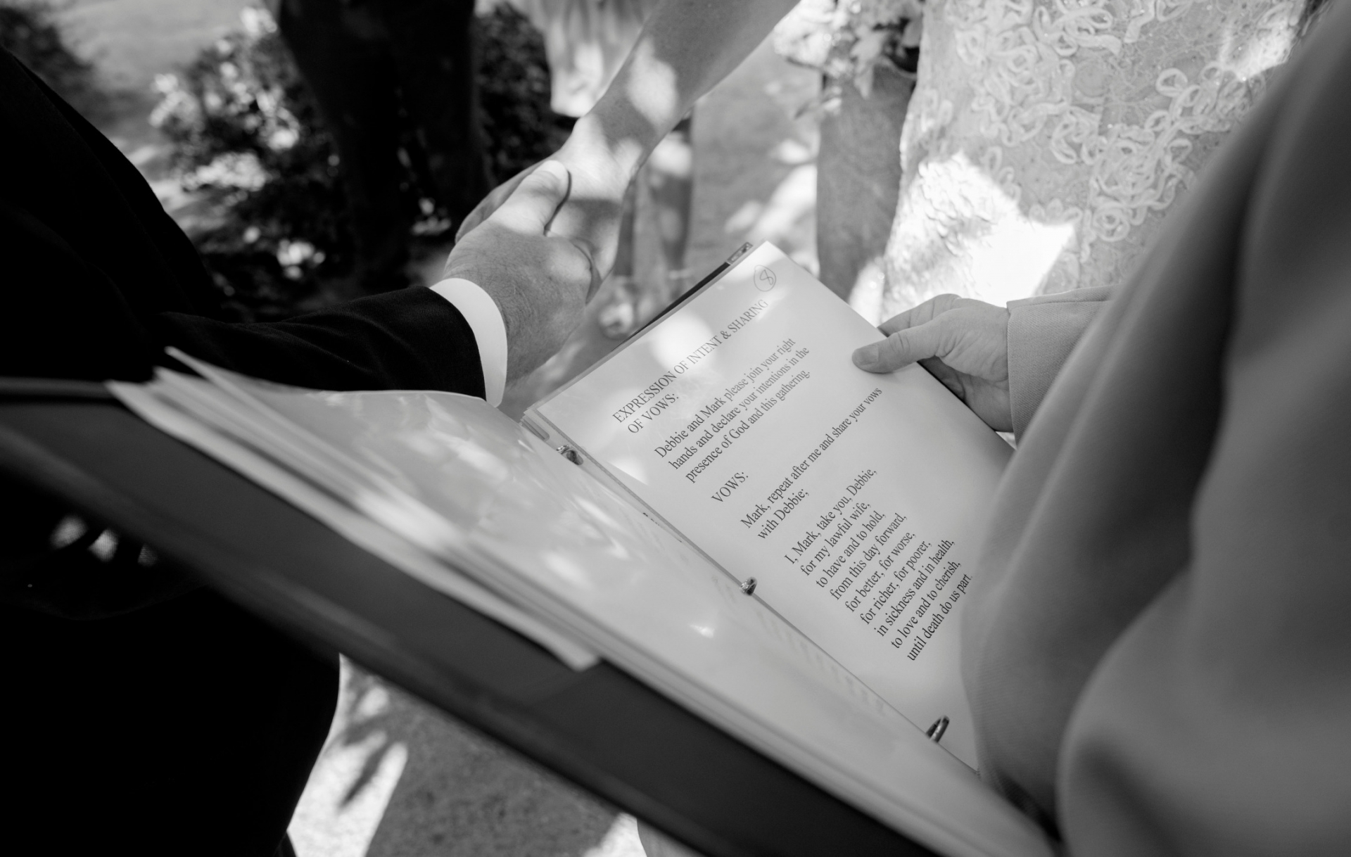 Japanese Friendship Garden Elopement Detail Image | We can see the officiant reading the vows as the bride and groom hold hands in front of the officiant's pages