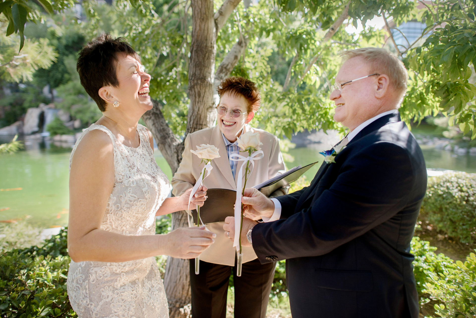 Japanese Friendship Garden Elopement Picture | The bride has a good laugh during the ceremony, and the groom and officiant can't help but smile with her