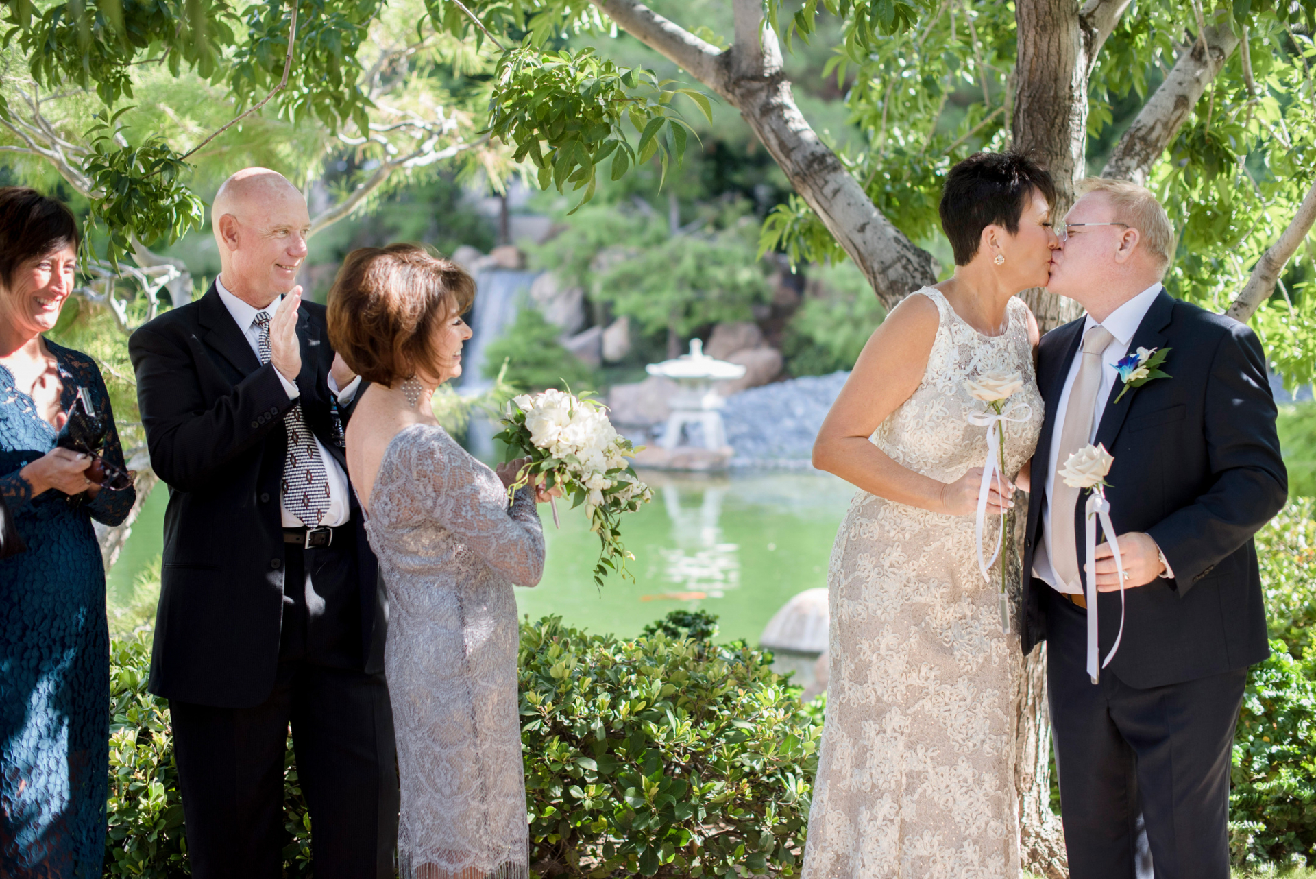 Japanese Friendship Garden Elopements - AZ Photographer | The small number of guests smile and applaud as the bride and groom finally share a kiss at the end of the ceremony