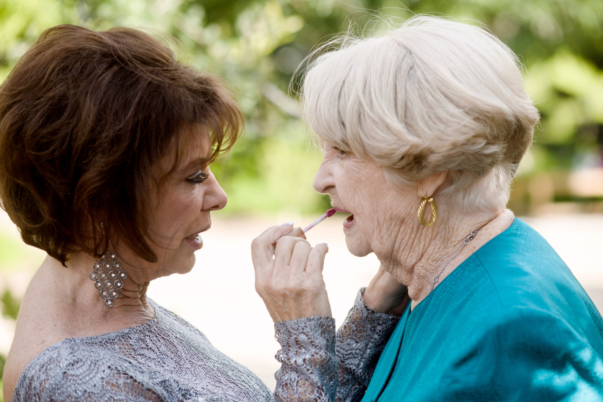 Japanese Friendship Garden Elopement Image - AZ Photography | A woman helps another reapply her lip gloss, unintentionally mirroring the other woman's open mouth as she puts it on
