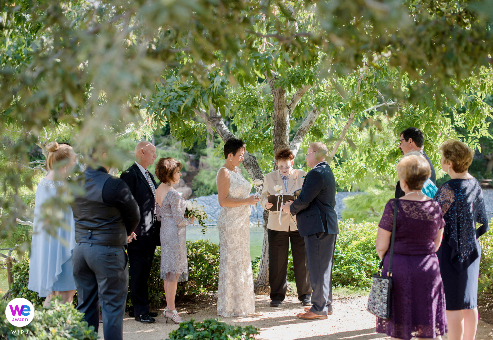 Japanese Friendship Garden, Phoenix, AZ Elopement Photo Story | The bride, groom, and guests stand under a tree during the ceremony. The guests watch while the officiant reads aloud