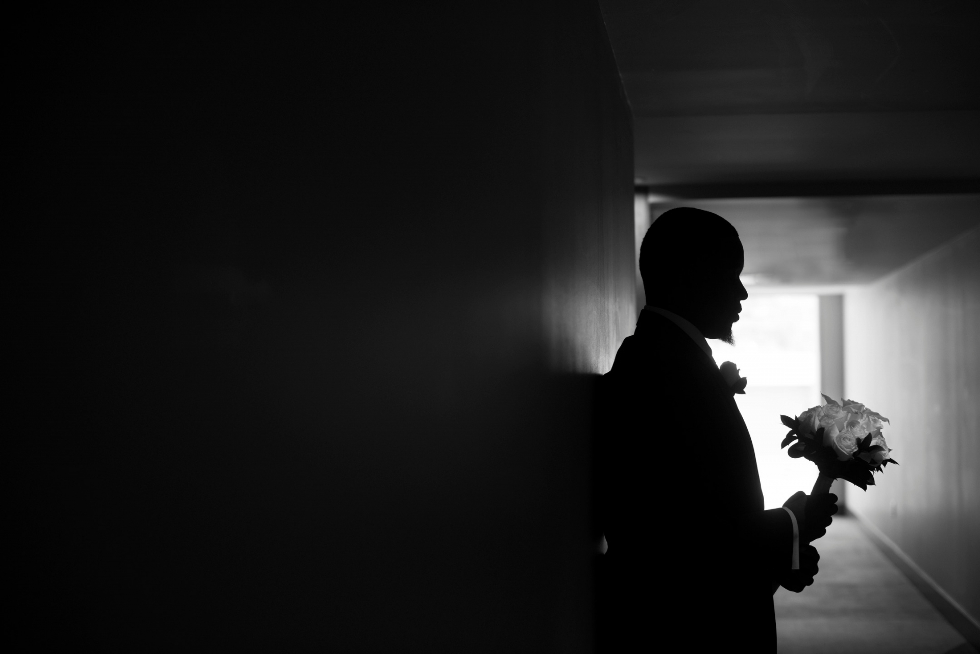 Mountain Shadows Resort Scottsdale, Arizona Elopement Photographer | With the bright light shining from behind him, we can only see the groom's silhouette as he stands in a hallway waiting for the bride as he holds her bouquet