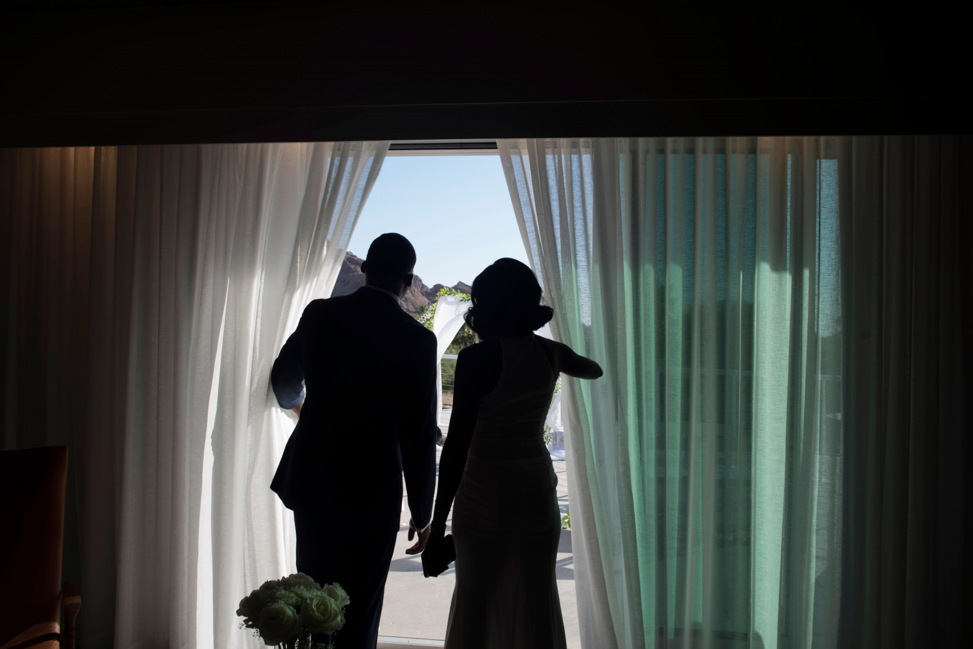 Mountain Shadows Resort Scottsdale Elopement, Arizona Photos | From inside the hotel room, the bride and groom stand together as they look out onto the bright balcony where they are about to be married