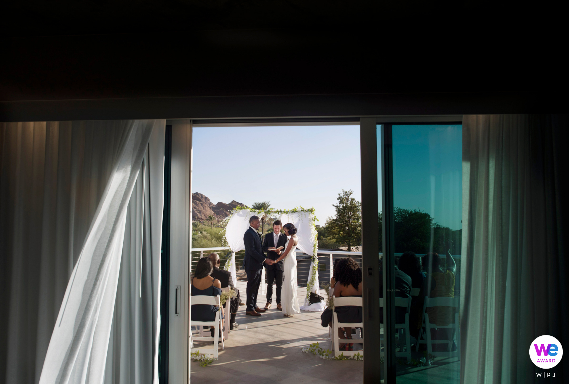 AZ Elopements | Mountain Shadows Resort Scottsdale, Arizona Elopement Photo | From inside the doors of a balcony, we can see the guests watching as the bride and groom stand at a floral arch in front of the officiant