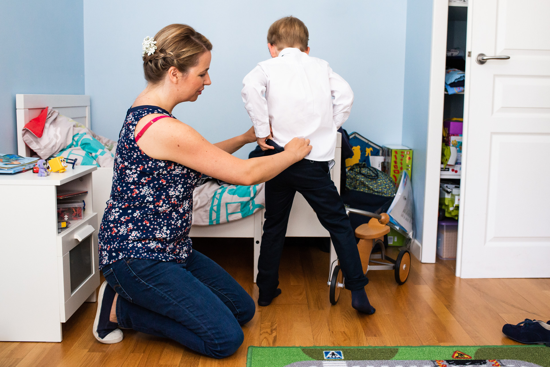 France Elopement Picture of Getting Ready | The attentive bride helps her son prepare