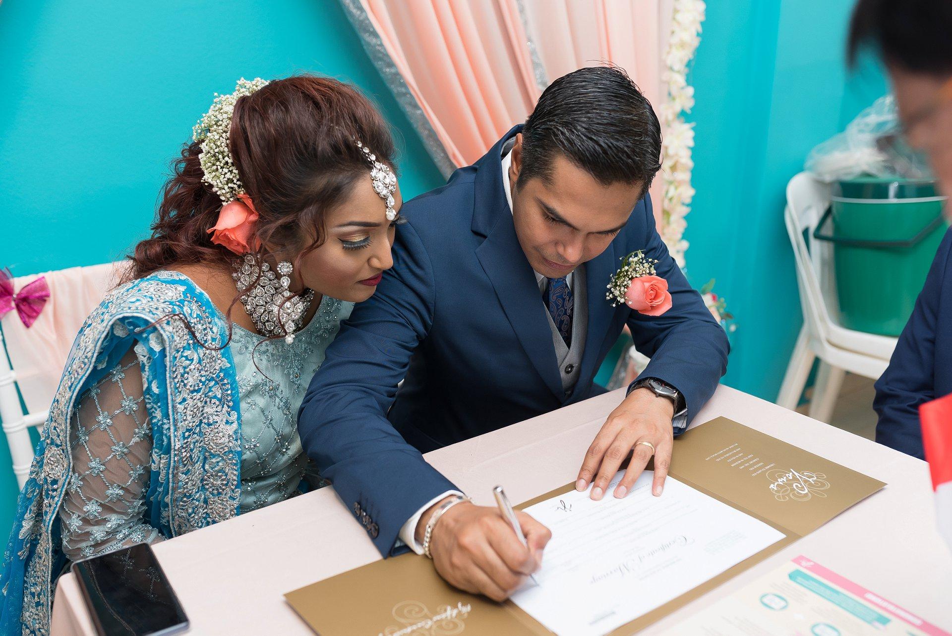 COVID-19 trouwfoto's van schaking in Singapore | zij gaan verder met het ondertekenen van de huwelijksakte van de Solemniser
