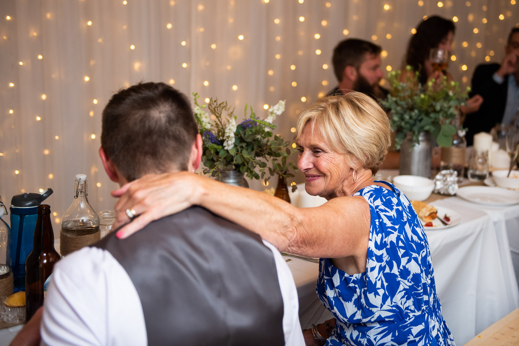 Garage Elopement Reception Party Photographer   the groom's mom shares a sweet moment with him at dinner after their wedding ceremony