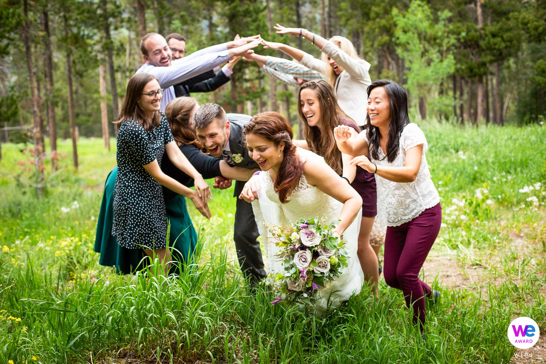 Nederland, Colorado Backyard Elopement Photography   Close friends goofed off with the couple all day, giving them well-wishing bum-pats on the way through the tunnel of hands