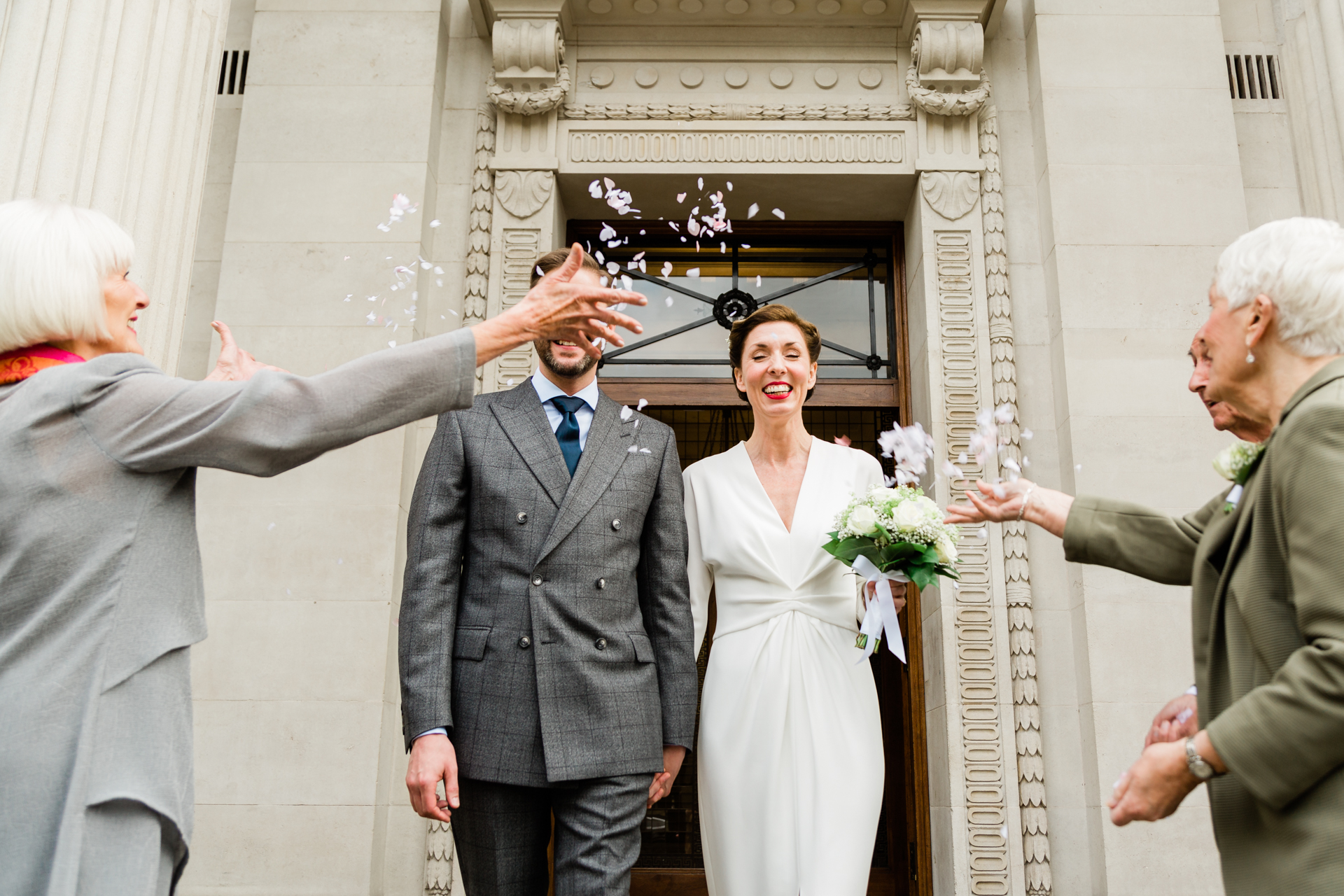 Central London Wedding Elopement Image | Confetti was thrown after the official vows, all three of their guests in the shot. Only three guests, and still a hand in front.