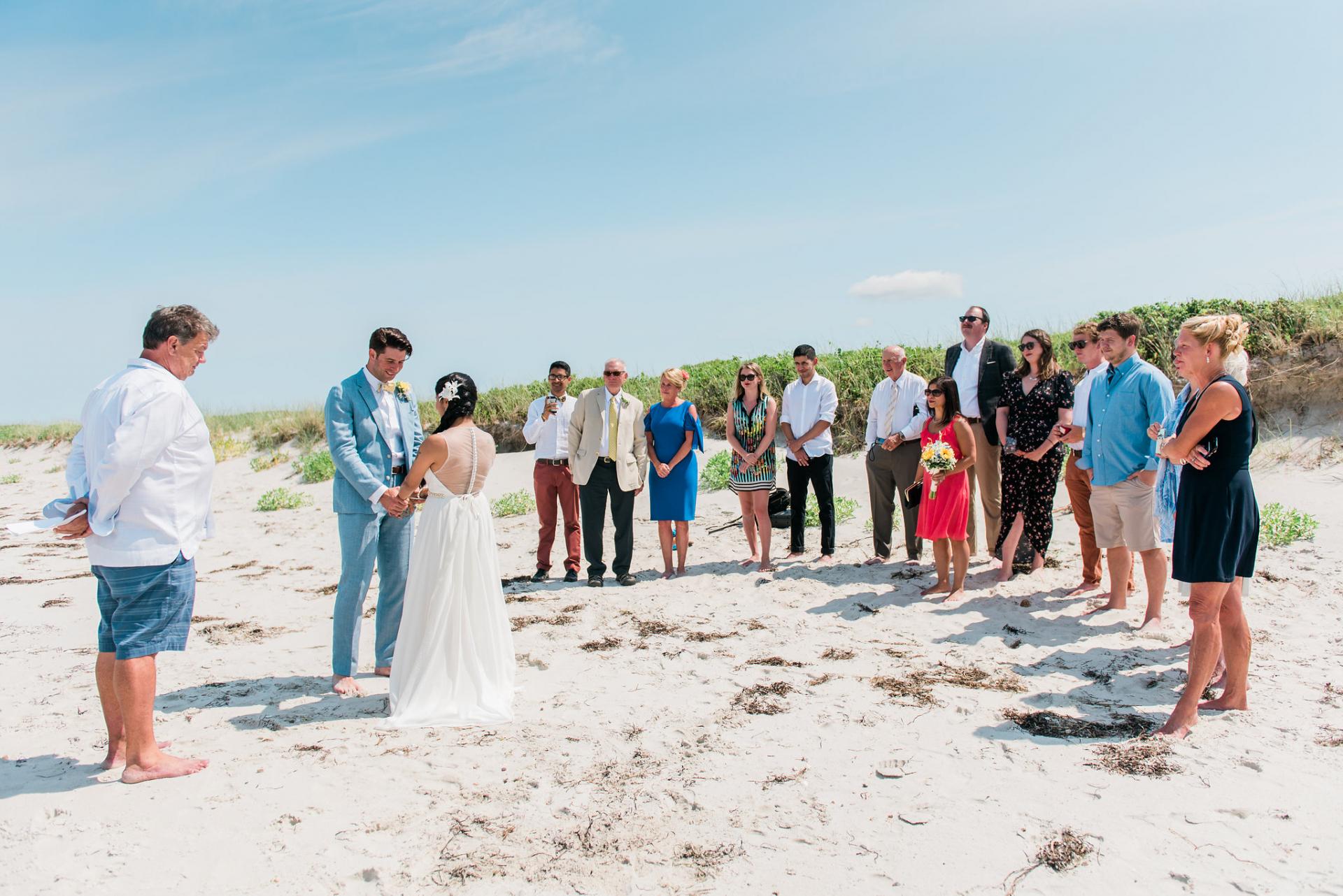 Falmouth, MA Strand Elopement Zeremonie Bild   Ein Familienmitglied leitet die kleine Zeremonie am Strand mit nur wenigen Familienmitgliedern und Freunden
