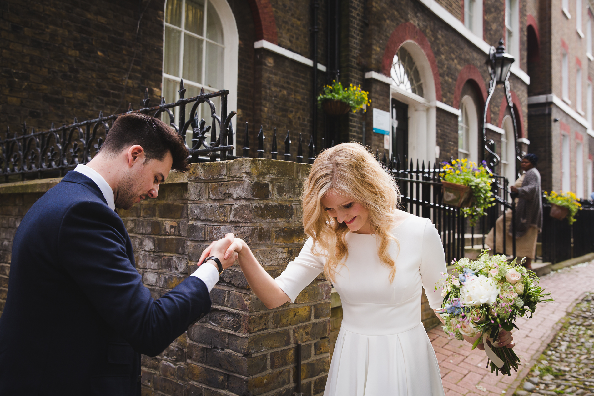 London Wedding Elopement Couple Image | a smiling bride crosses the cobblestoned streets