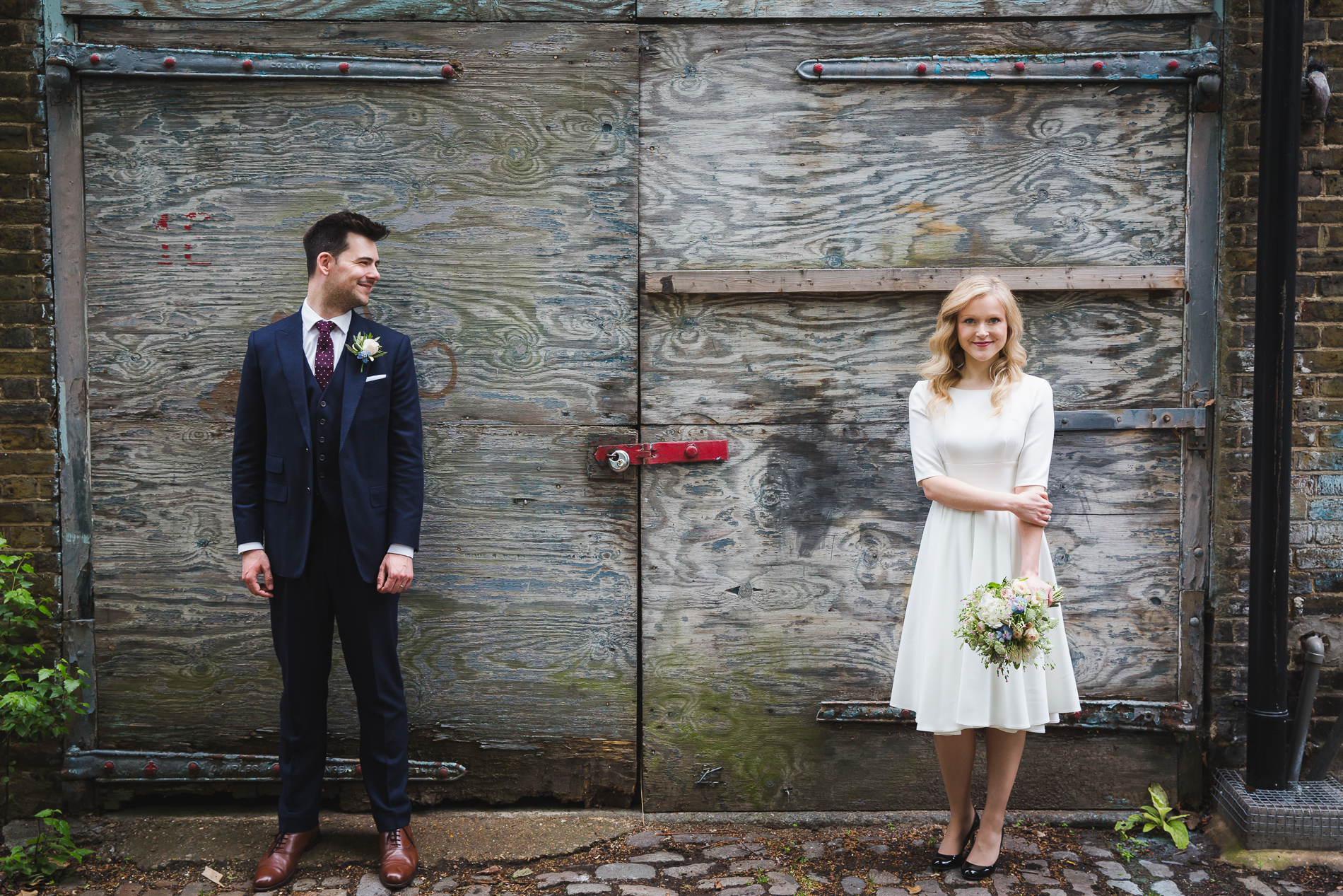 London Elopement Couple Urban Portrait | a knee-length wedding dress makes a stark contrast to the urban terrain