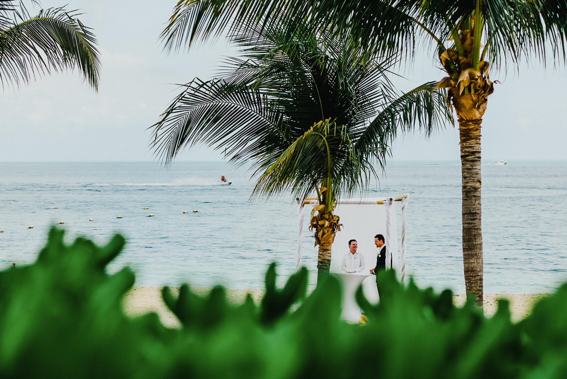 Excellence Playa Mujeres, Cancun, México Imagem de casamento na praia | Palmeiras balançam na brisa e turistas brincam nas ondas