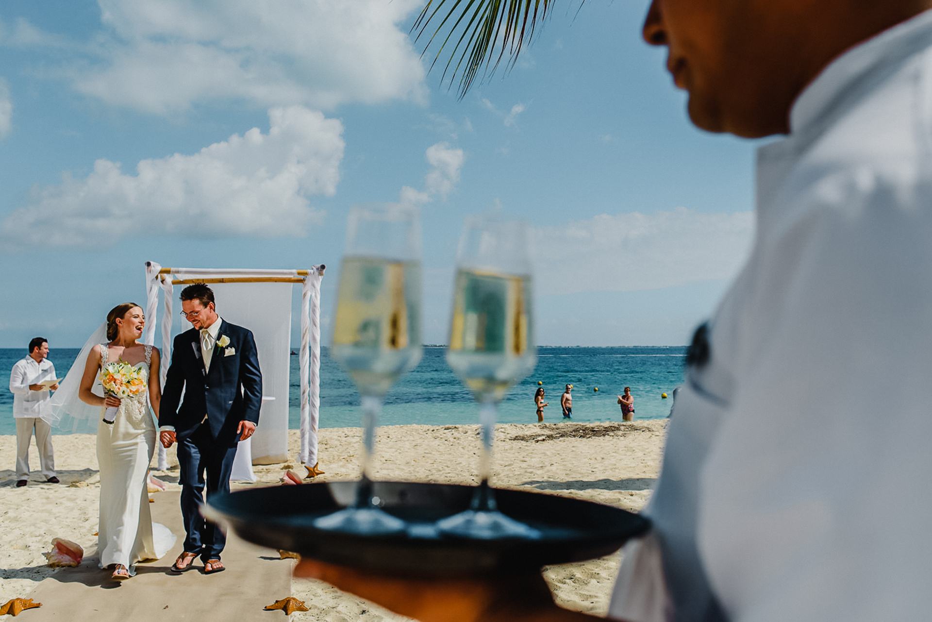 Cancun Beach Elopement Ceremony Image | The couple strolls down the sandy aisle in flip-flops