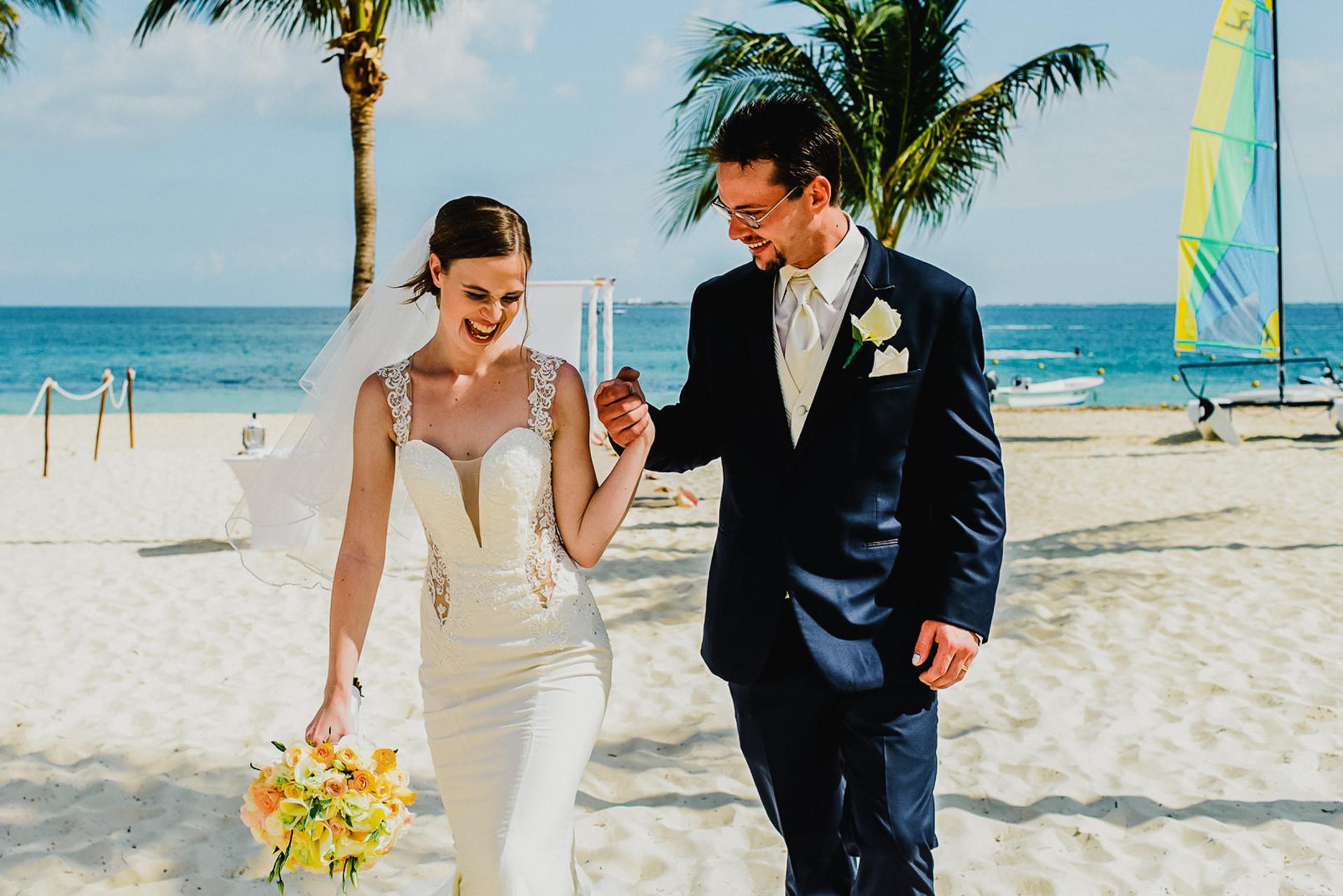 Imagem de casal do México desde a fuga da praia | O casal recém-casado aperta as mãos e compartilha uma risada