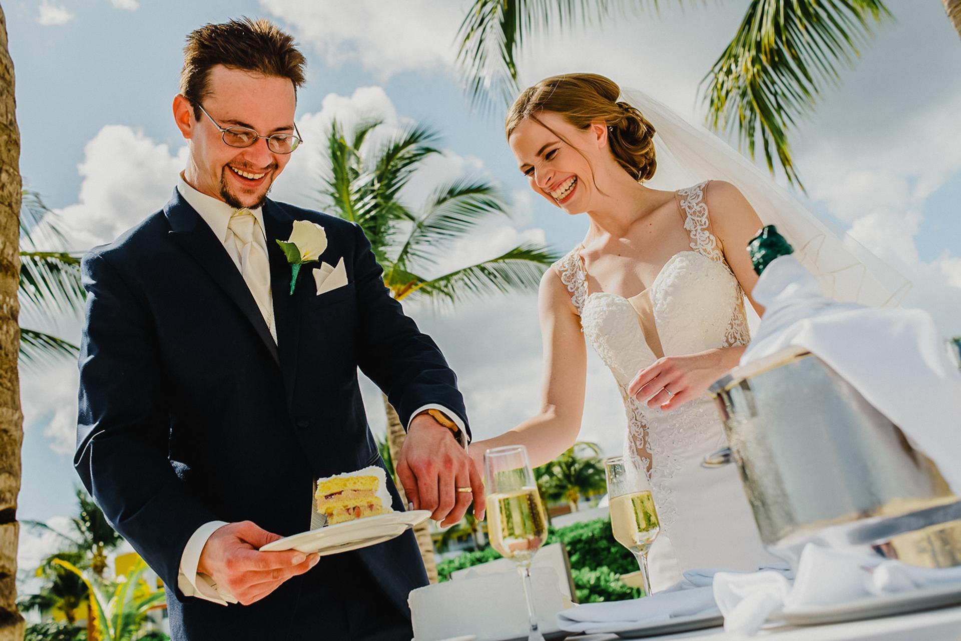 Imagem de casal casamento Cancun praia | o noivo serve a primeira fatia de bolo de casamento
