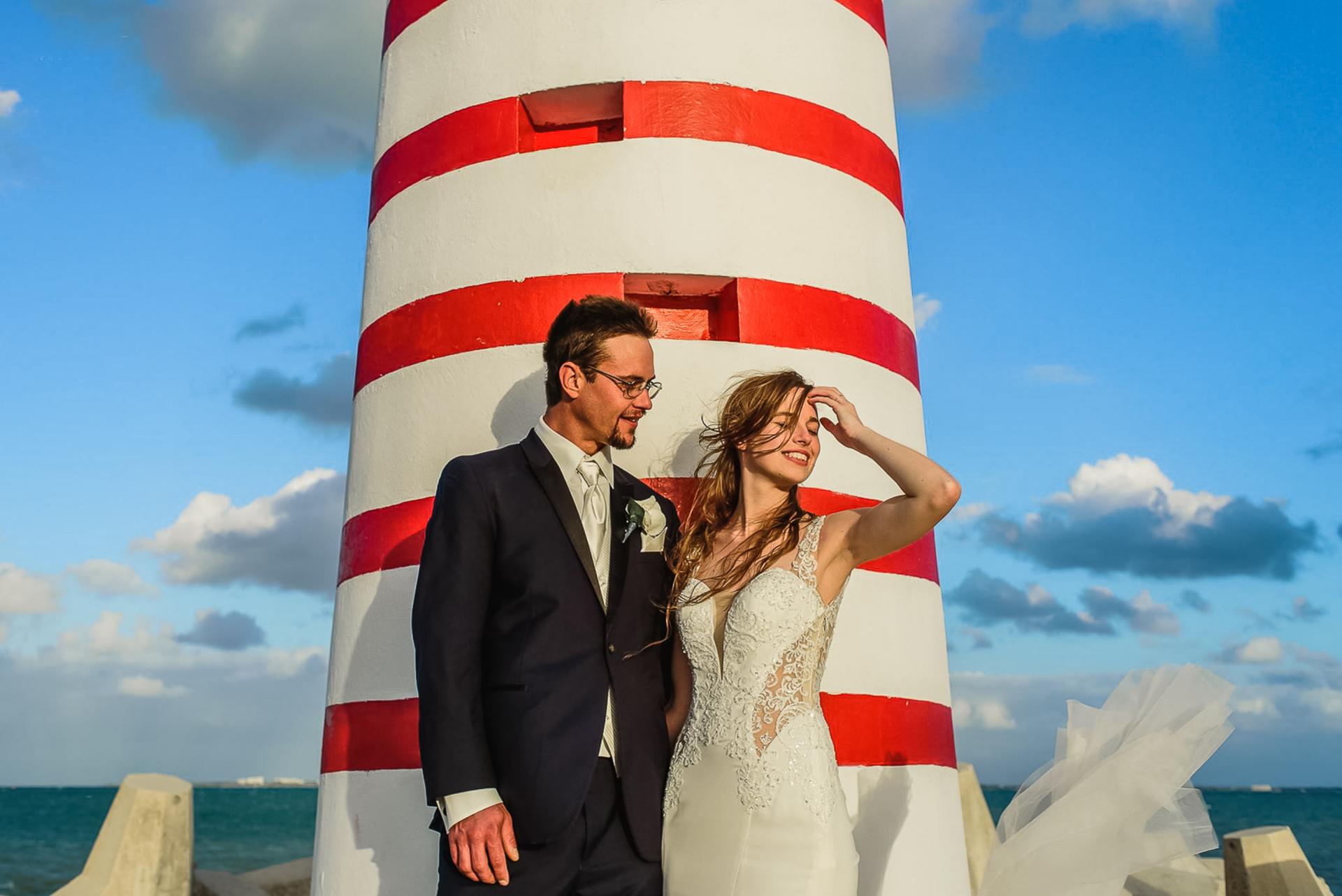Retrato de casal de casamento na praia do méxico | a noiva e o noivo passam um breve momento perto do farol listrado da praia
