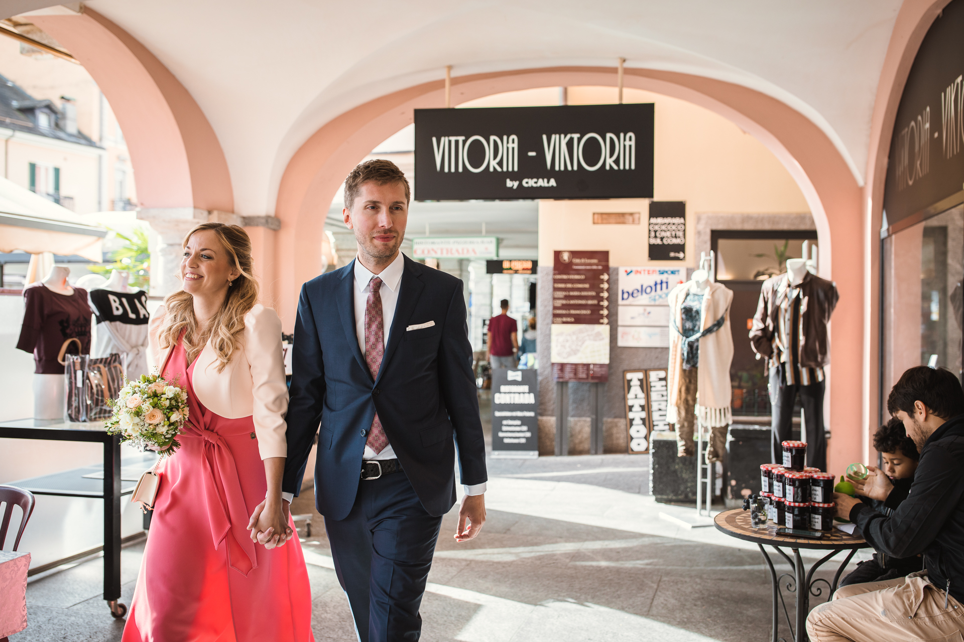 Locarno City Hall, Switzerland Elopement Photography | the bride and groom stroll hand in hand past shop displays in Locarno