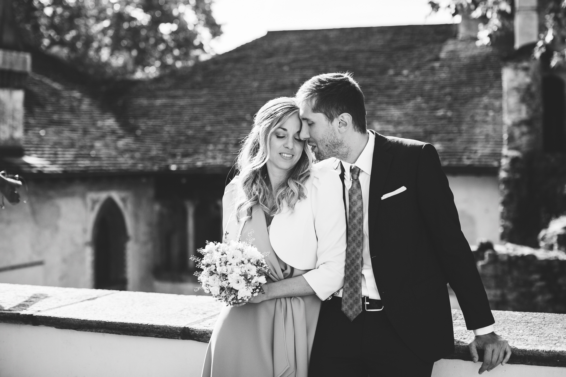 Switzerland Elopement Portrait in Black and White | the couple recline against a low wall