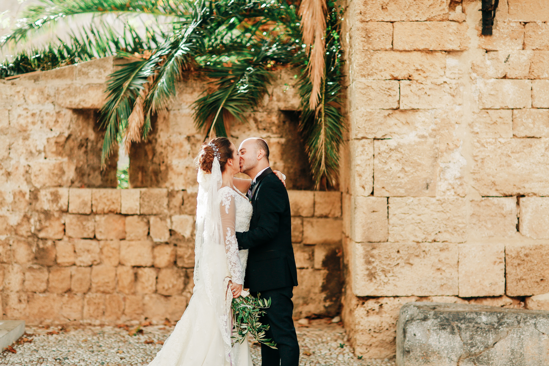 Greece Wedding Photographer, Picture of the Couple Kissing | vibrant palm fronds in Rhodes frames the newlyweds as they share a kiss