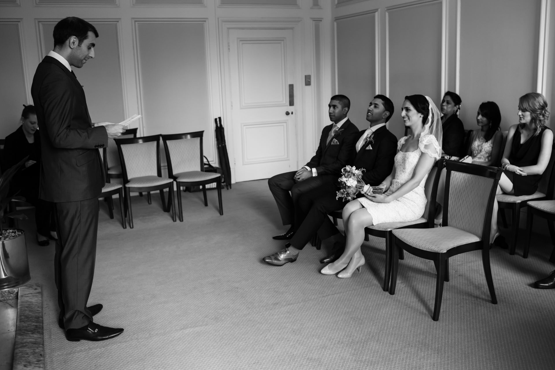 Town Hall of Westminster Civil Ceremony - London Wedding Photo | a reading during the ceremony as the bride and groom sit among their family