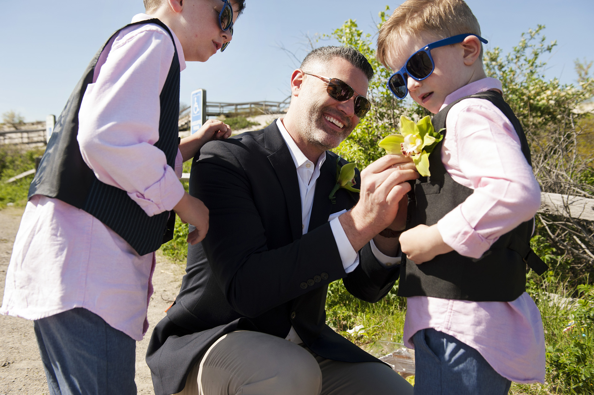 Ipswich, Massachusetts Elopement Photos   The groom pinning boutonnieres on the bride's children in the parking lot