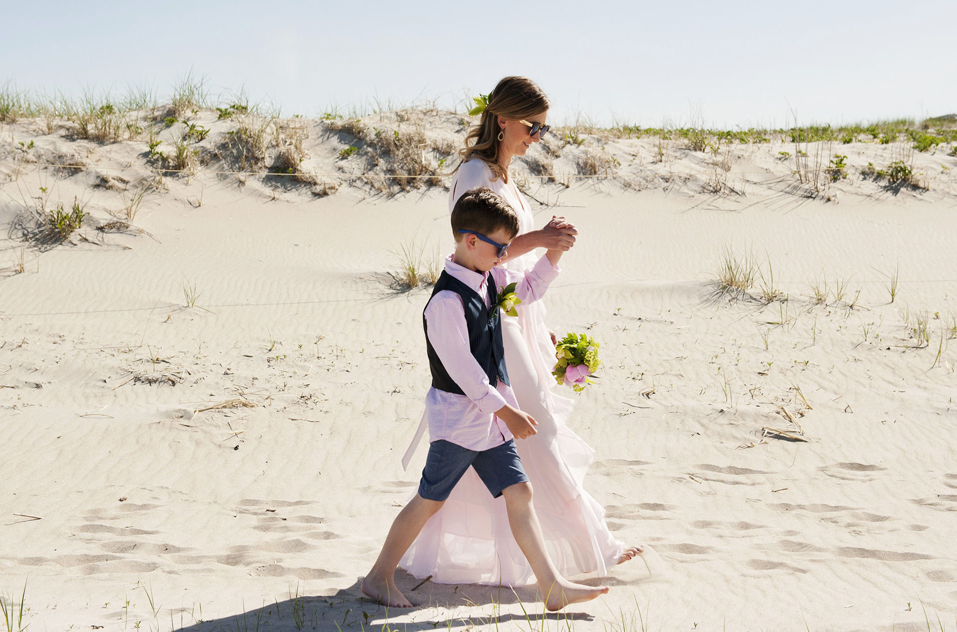 Ipswich, MA Beach Elopement Photographer   The bride and her son hold hands en route to the ceremony location