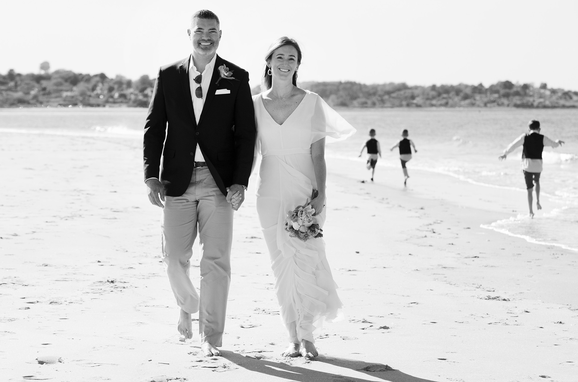 MA Wedding Elopement - Beach Sand Portrait   The couple strolling on the beach with the boys running in the background