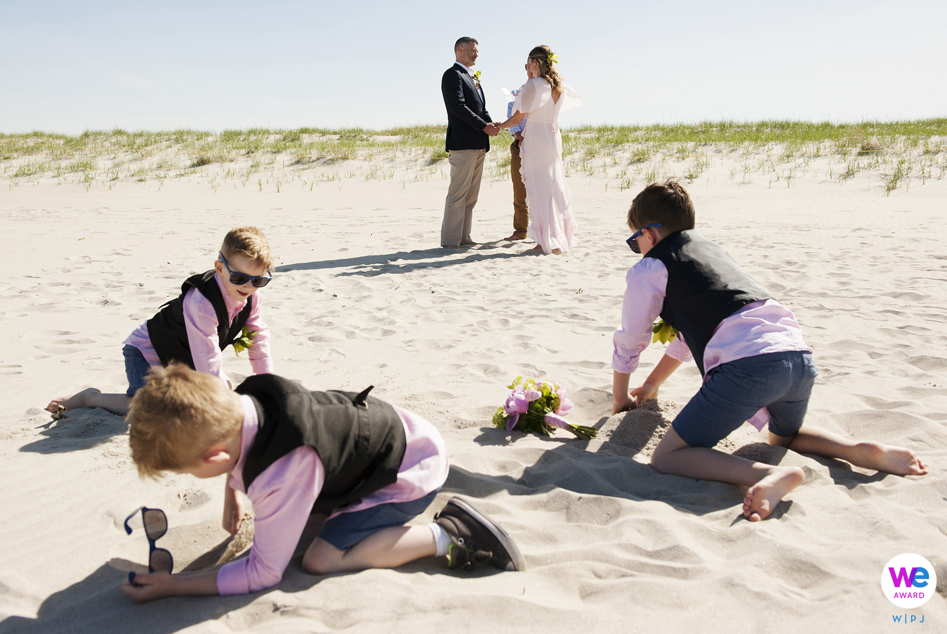Crane Beach, Ipswich, MA Beach Elopement Ceremony Photo Story   The bride's 3 young boys digging in the sand with the ceremony taking place in the background